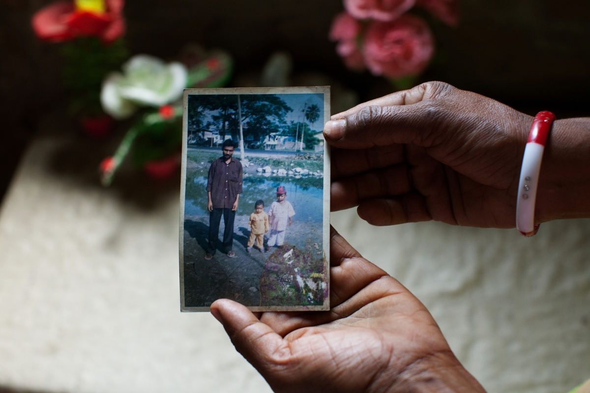 Mamtaj Begum holds a photograph of her husband, Mahuruddin, who is held in a detention center in Tezpur. Mahuruddin was photographed with his son and nephew.