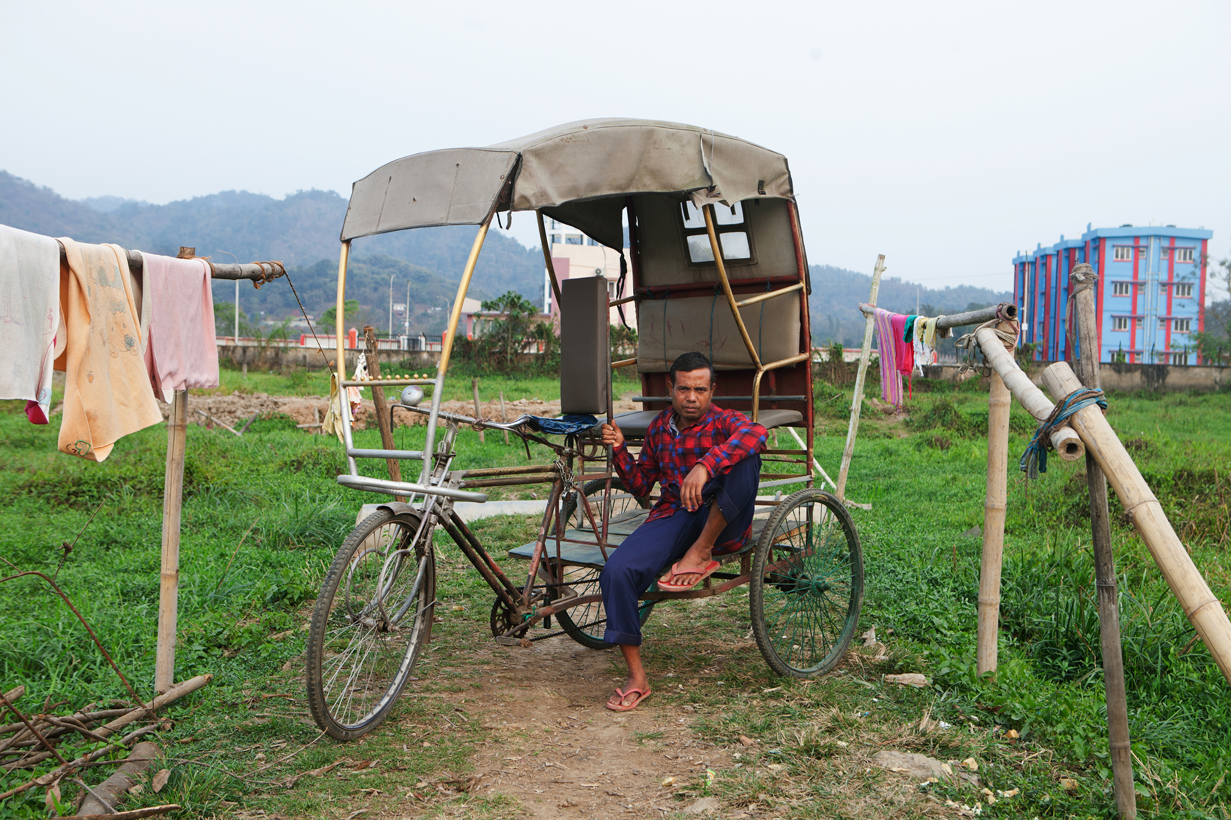 Nur Hussein, who was imprisoned and separated from his family for a year and a half before winning his citizenship case, rests on his rickshaw in a field adjacent to his home