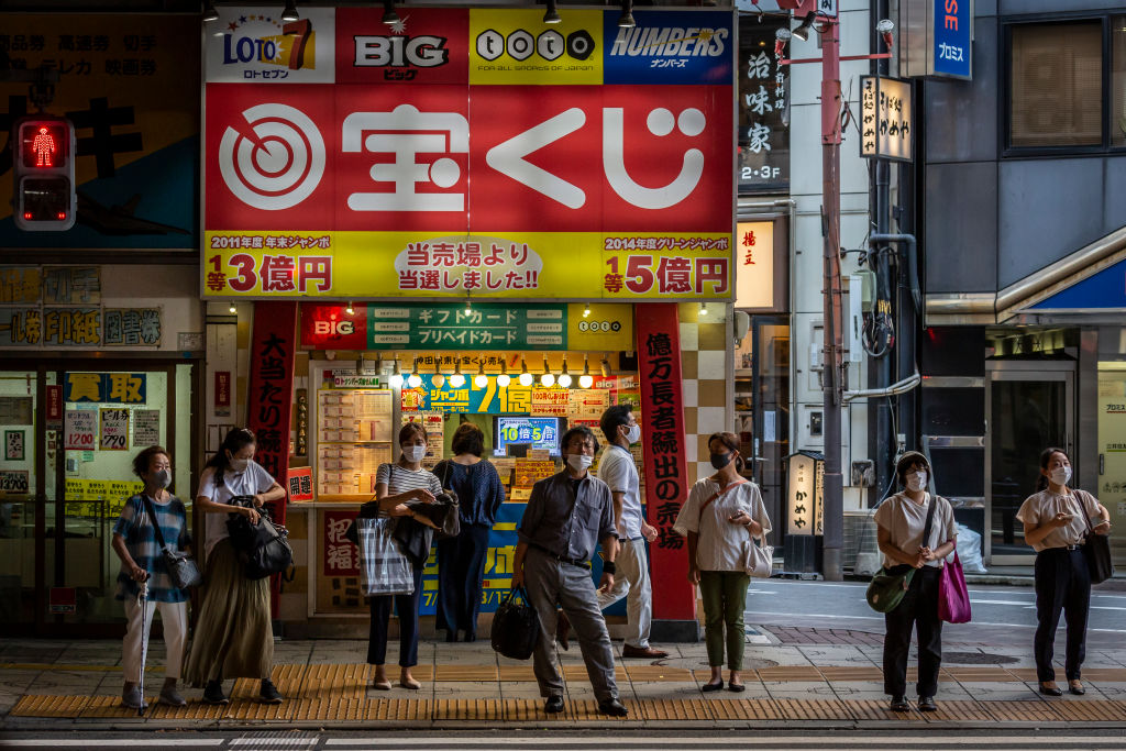 People wearing face masks wait to cross a street on July 28, 2021 in Tokyo, Japan. Tokyo metropolitan government reported 3,177 new coronavirus cases on Tuesday, an increase on yesterday and the highest number of infections recorded so far for the city.