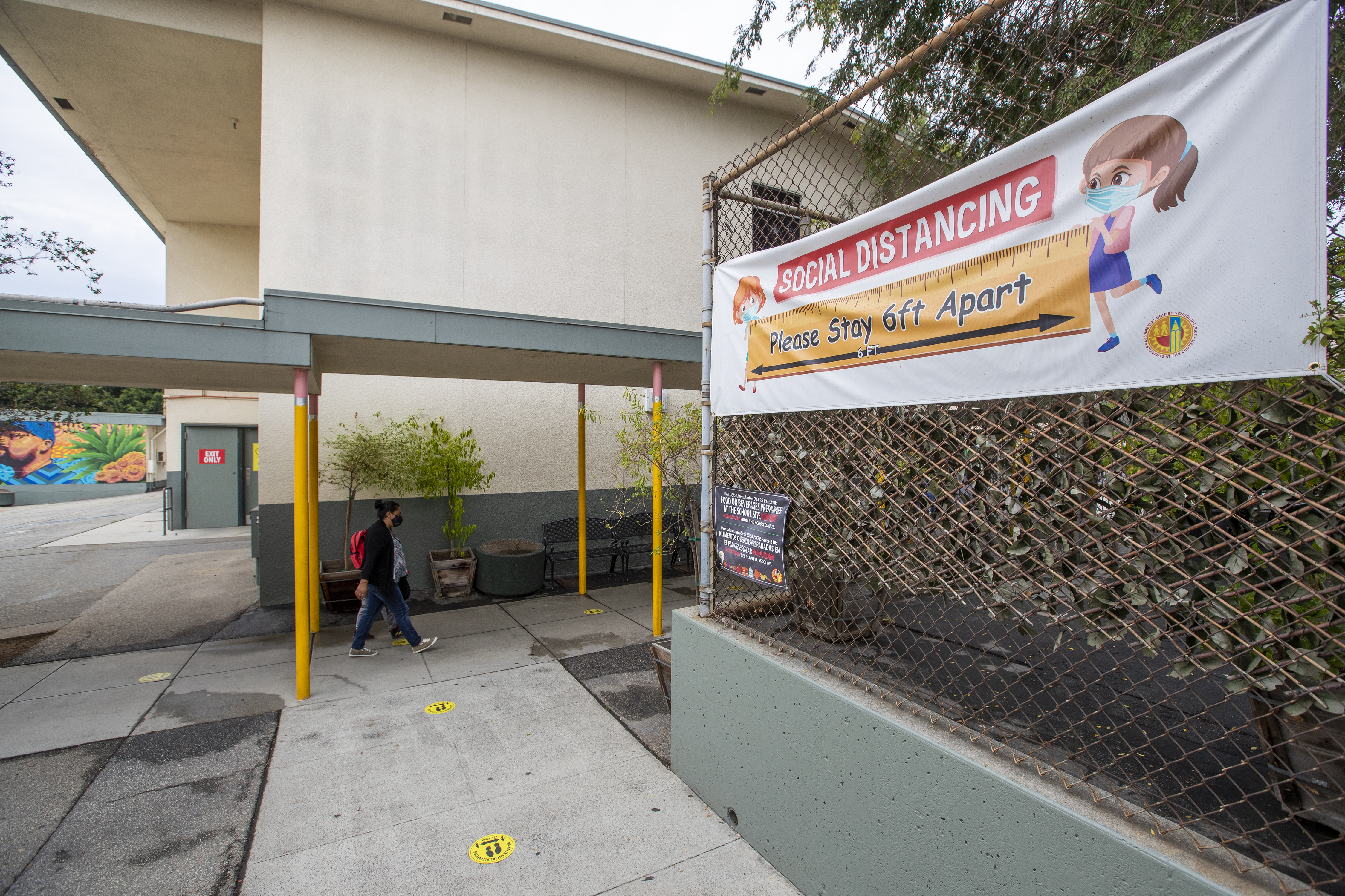 Daniel Cano, 5, and his mom, Sonia Cano, walk past COVID-19 safety signs at Euclid Avenue Elementary School in Los Angeles on July 26, 2021.