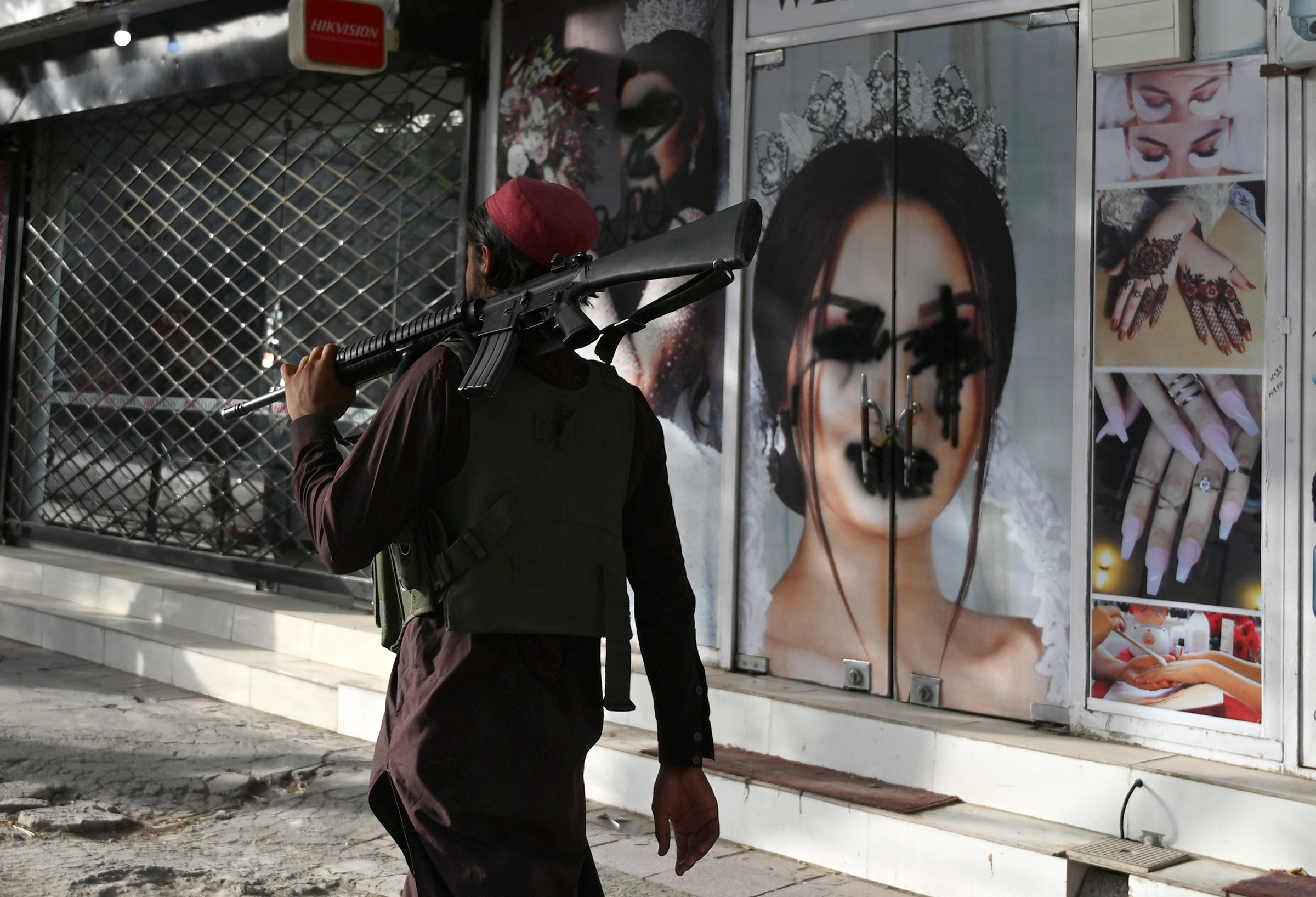 A Taliban fighter walks past a beauty salon with images of women defaced using spray paint in the Shar-e-Naw area of Kabul on Aug. 18.