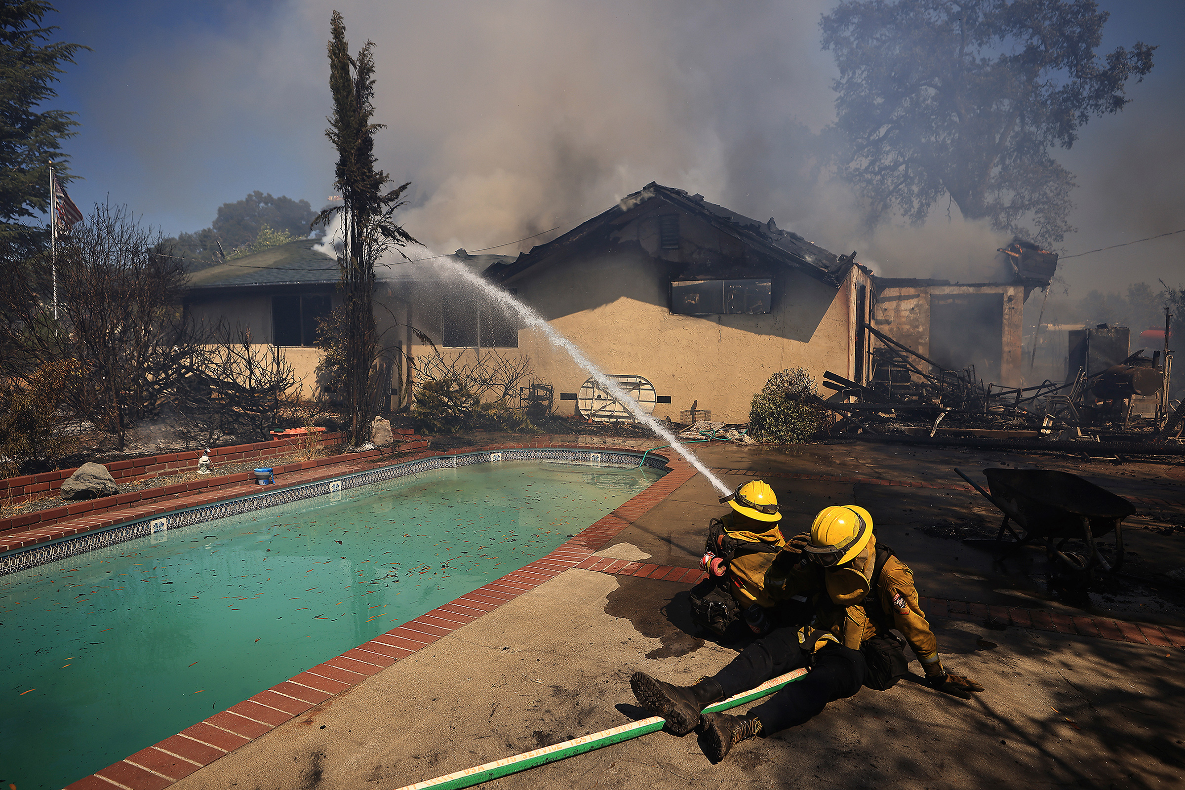 Firefighters take a defensive stand against a home burning in Redwood Valley, Calif., ignited by an 80 acre wind whipped brush fire fed by tinder dry conditions on July 7.