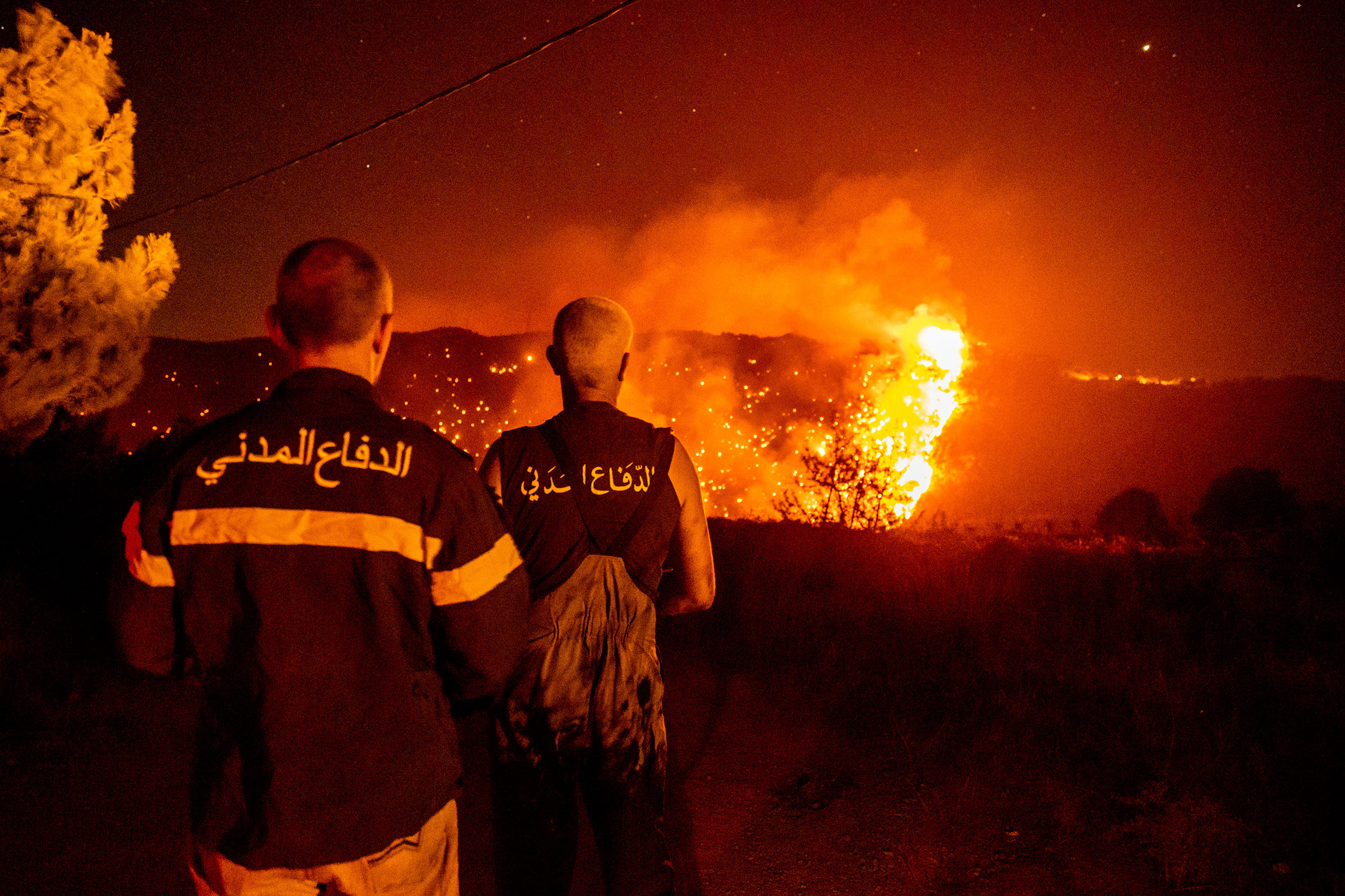 Civil Defense personnel monitor a wildfire burning through hills in Qobayat, Lebanon on July 28. A Lebanese teenager was killed as he joined volunteers battling to fight the fire.