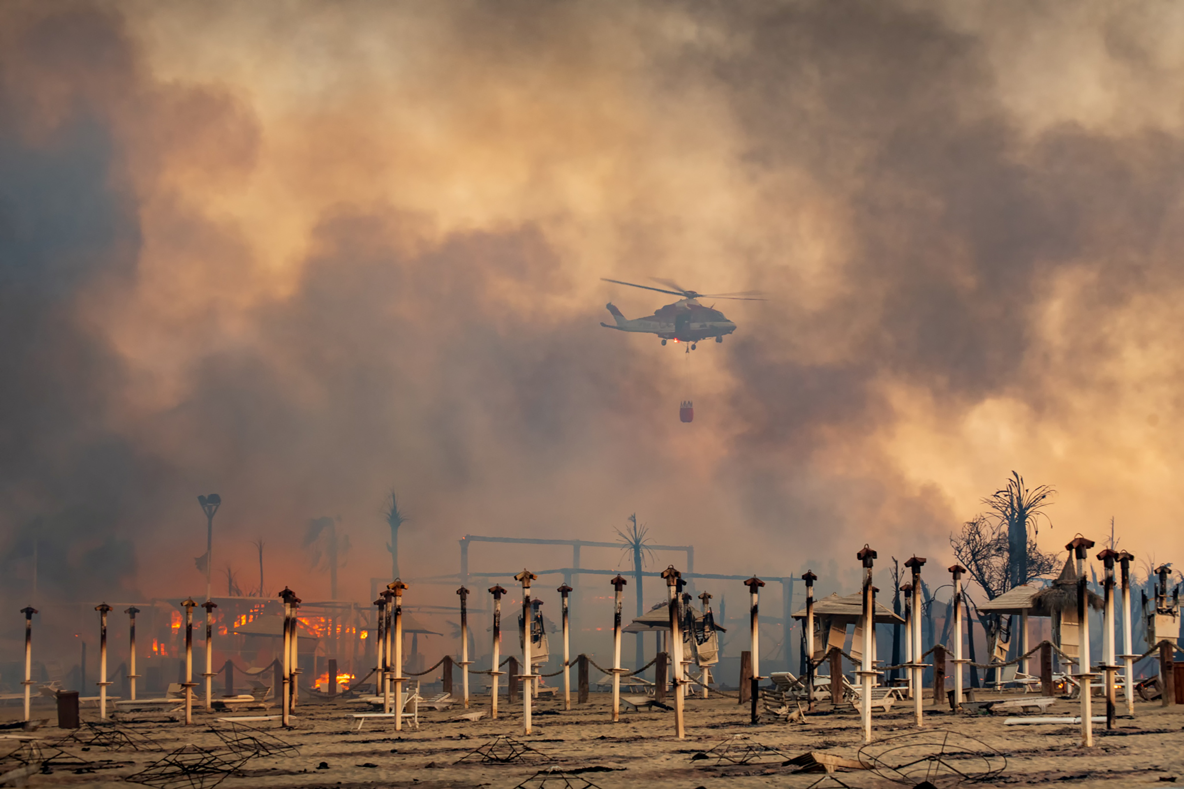 A helicopter flies above a fire at Le Capannine beach in Catania, Sicily, Italy on July 30.