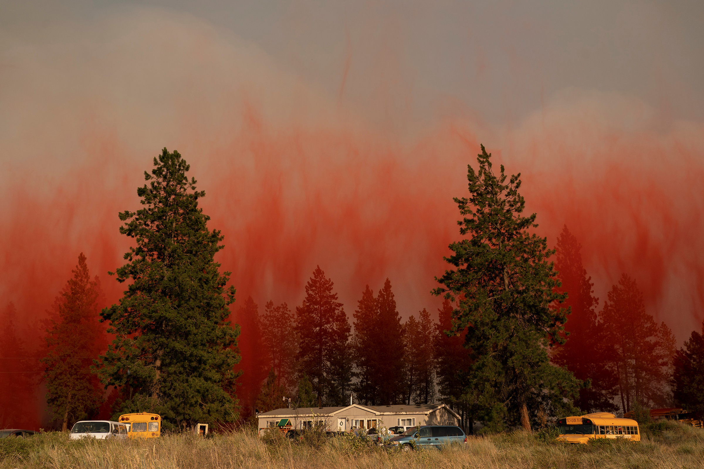 Fire retardant dropped from an airplane falls to the ground near the Chuweah Creek Fire as wildfires devastate Nespelem, Wash. on July 14.