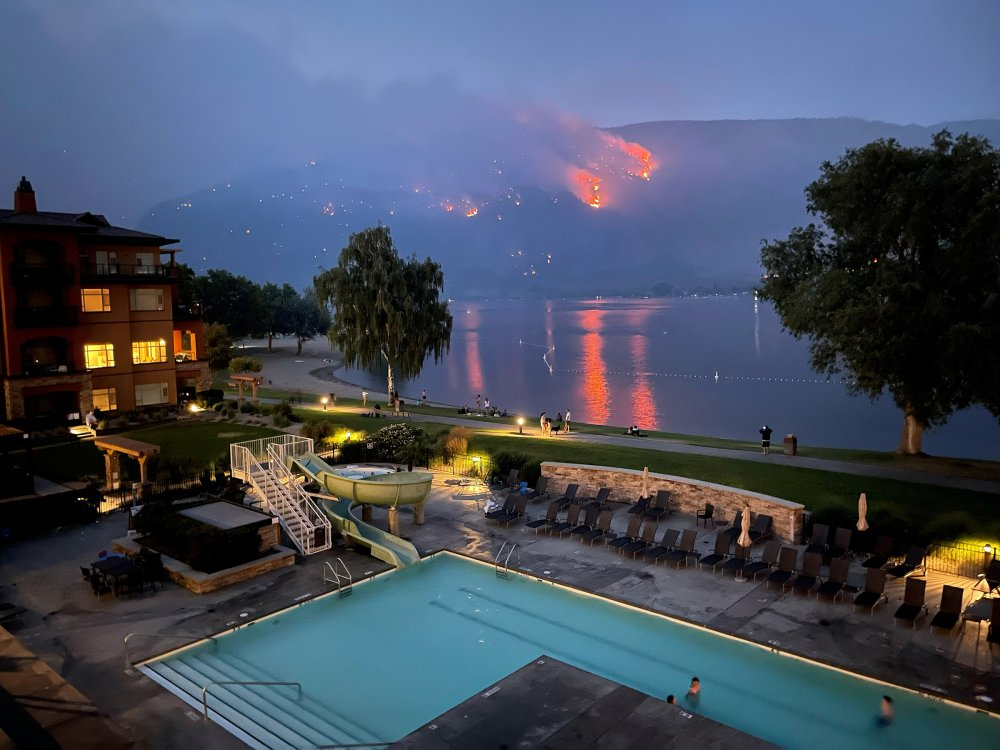 View of a beach resort as a wildfire burns on a hillside in Osoyoos, British Columbia, Canada, on July 20.