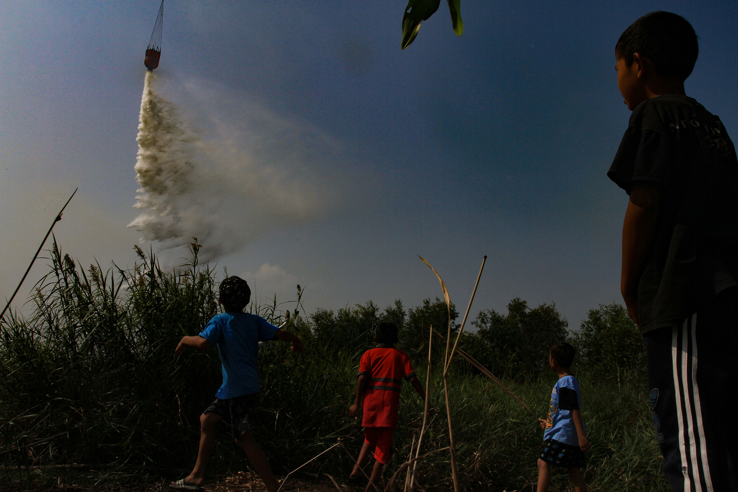 Children watch a helicopter dumping water on burning peatland at Palem Raya village in Ogan Ilir district, South Sumatra, Indonesia, on July 31.