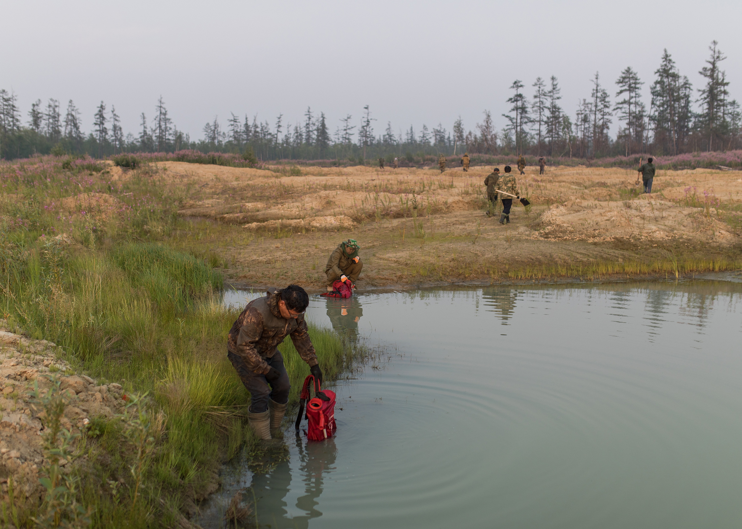 Volunteers fill firefighting satchels with water, at a source near Magaras.