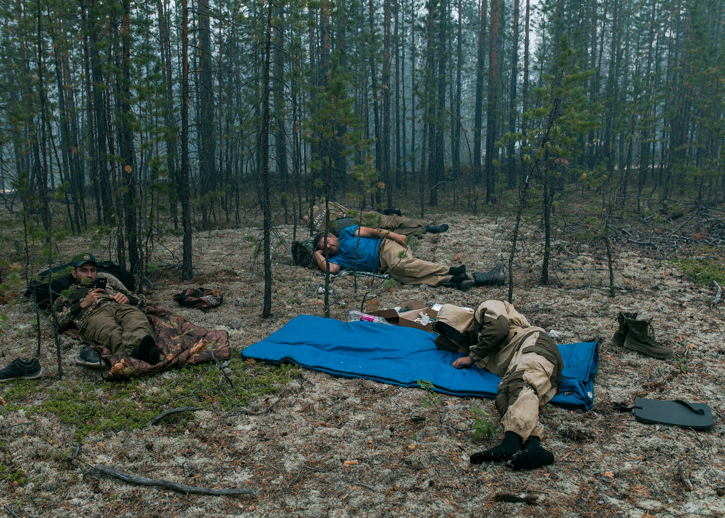 Firefighters of the Ministry of Emergency Situations of the Russian Federation resting after putting out small fires near the village of Dikimdya, on July 15.