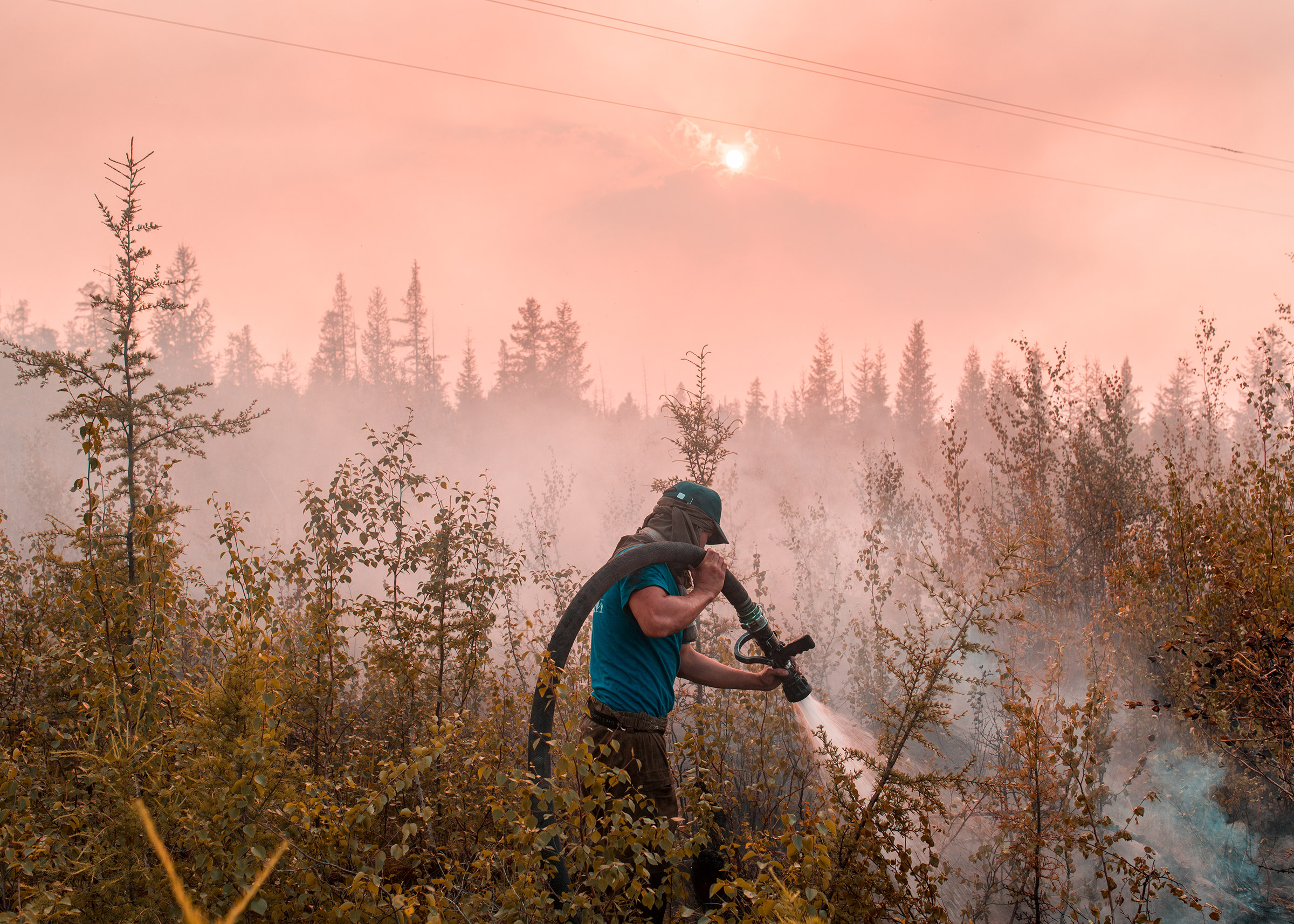 A firefighter extinguishes a grassroots fire near Kyuerelyakh.
