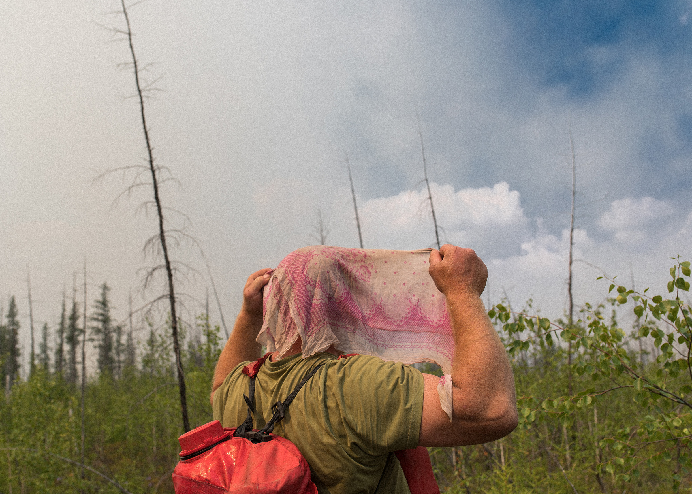 An employee of yhe Aerial Forest Protection Service of the Russian Federation puts a wet handkerchief on his head—an effective DIY protective against the dangers of wildfire smoke.