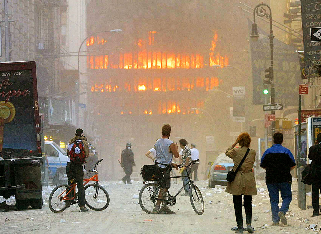 People walk in the street in the area where the World Trade Center buildings collapsed on Sept. 11, 2001