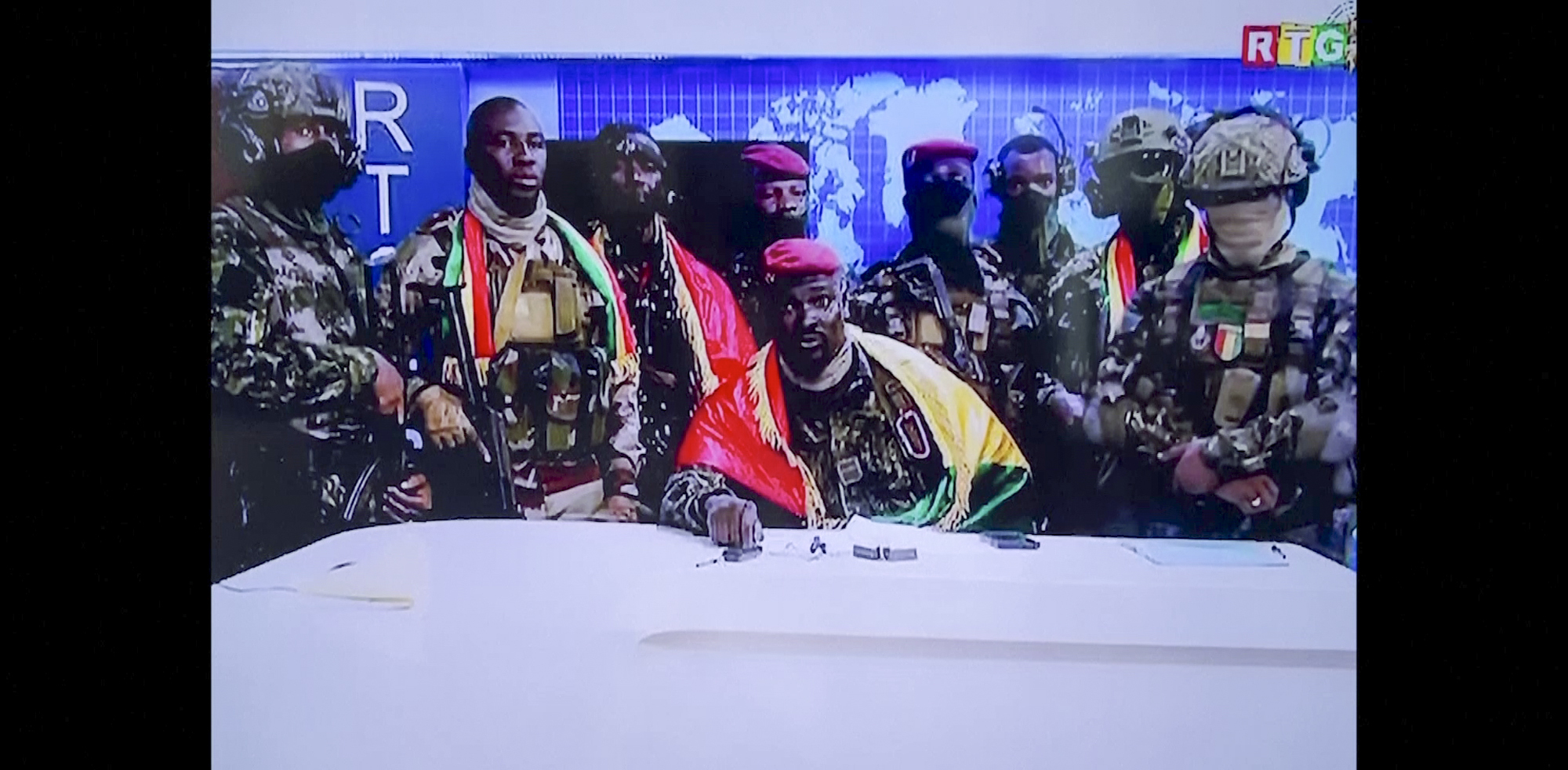 In this image made from video, Col. Mamadi Doumbouya, center, commander of the army's special forces unit, surrounded by others and draped in a Guinean flag, makes an address to the nation from state television headquarters in the capital Conakry, Guinea Sunday, Sept. 5, 2021.