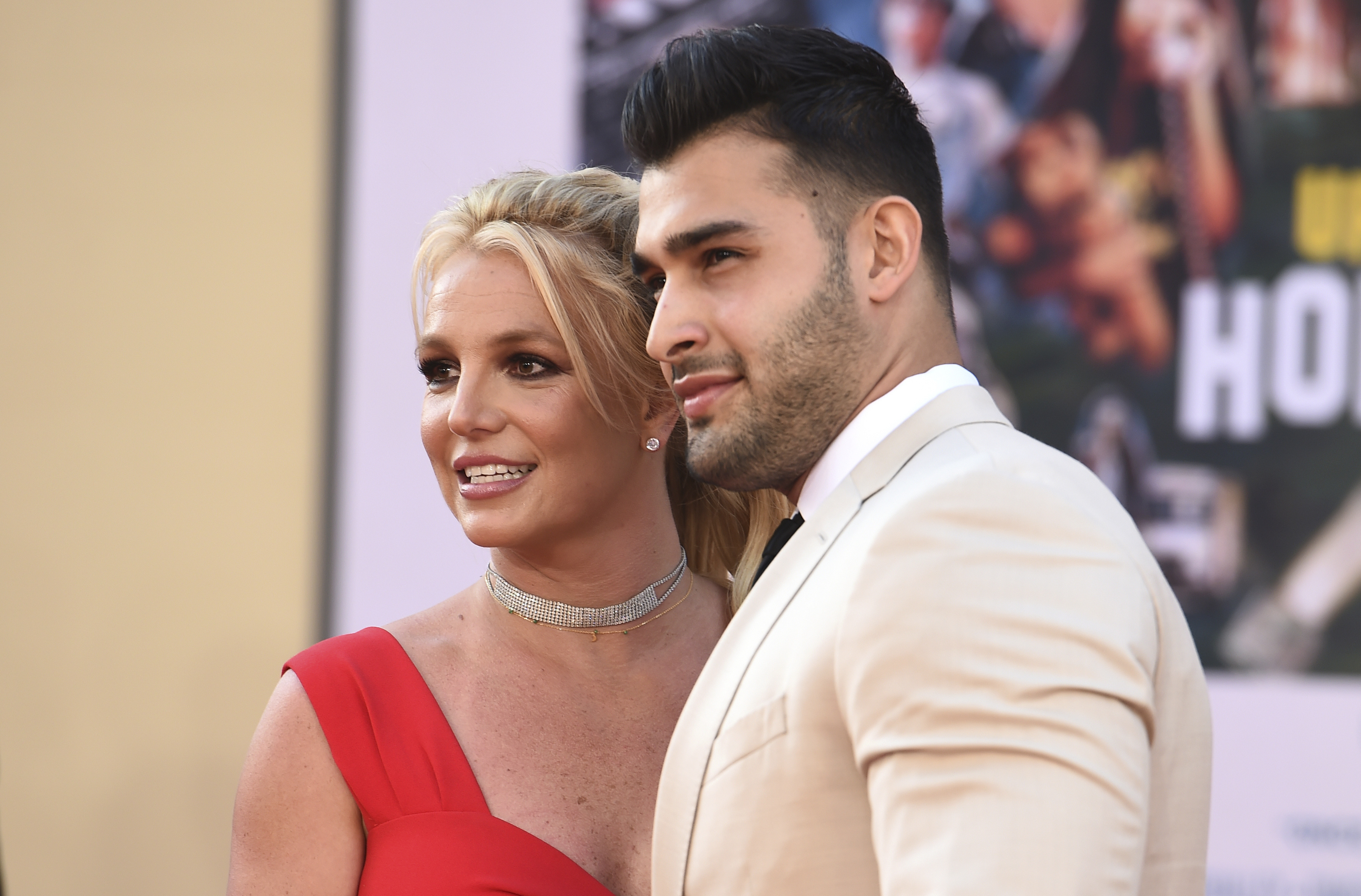 """Britney Spears and Sam Asghari arrive at the Los Angeles premiere of Once Upon a Time in Hollywood, at the TCL Chinese Theatre, Monday, July 22, 2019. Spears announced on Instagram on Sunday, Sept. 12, 2021, that she and Asghari are engaged. The couple met on the set of her """"Slumber Party"""" music video in 2016."""