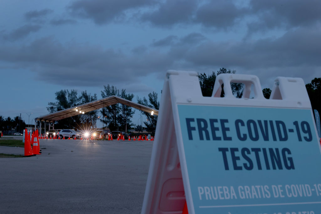 Healthcare workers at a 24-hour drive-thru site set up by Miami-Dade and Nomi Health in Tropical Park administer COVID-19 tests  in Miami, Florida, on August 20, 2021.