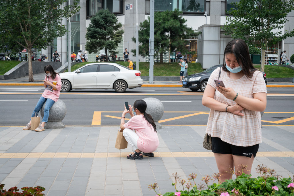 Pedestrians use their smartphones by the street in Beijing, China on July 16, 2021.