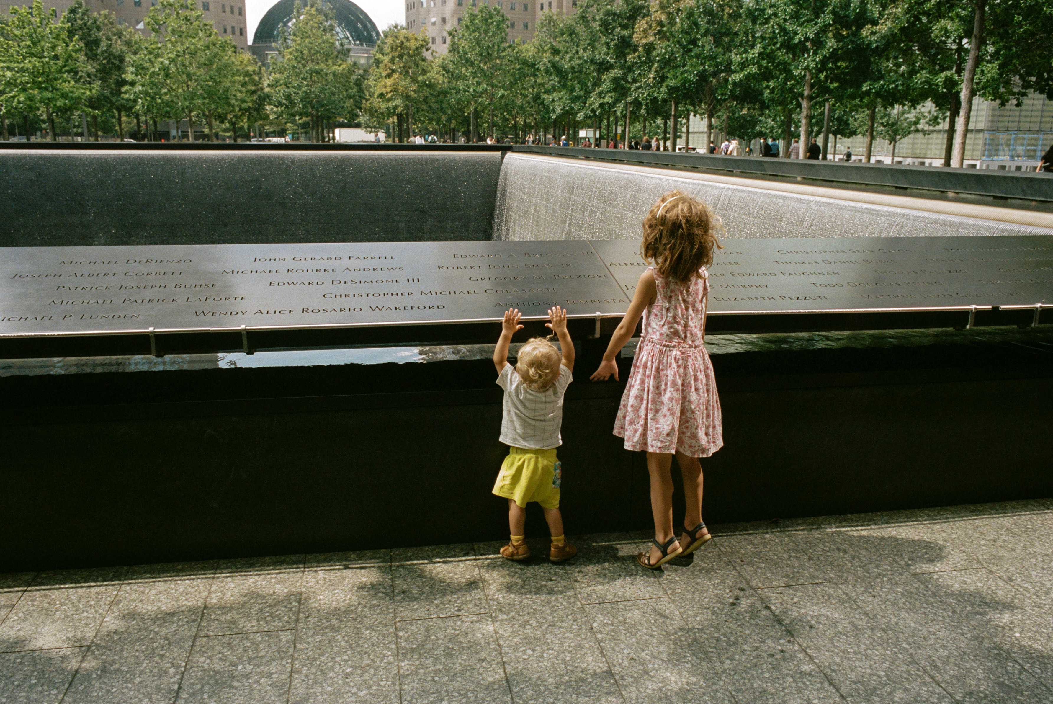 Children strain for a look over the lip of the 9/11 Memorial reflecting pool, Aug. 31, 2021.