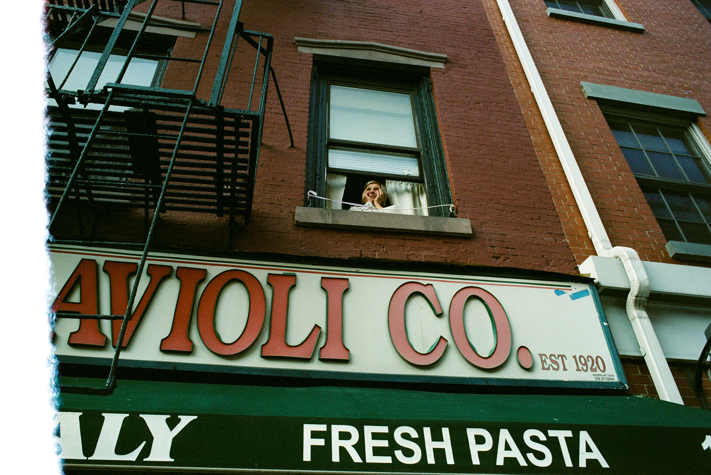 A woman in Little Italy looks out over the intersection of Mulberry and Grand Streets during the pandemic, May 14, 2020.