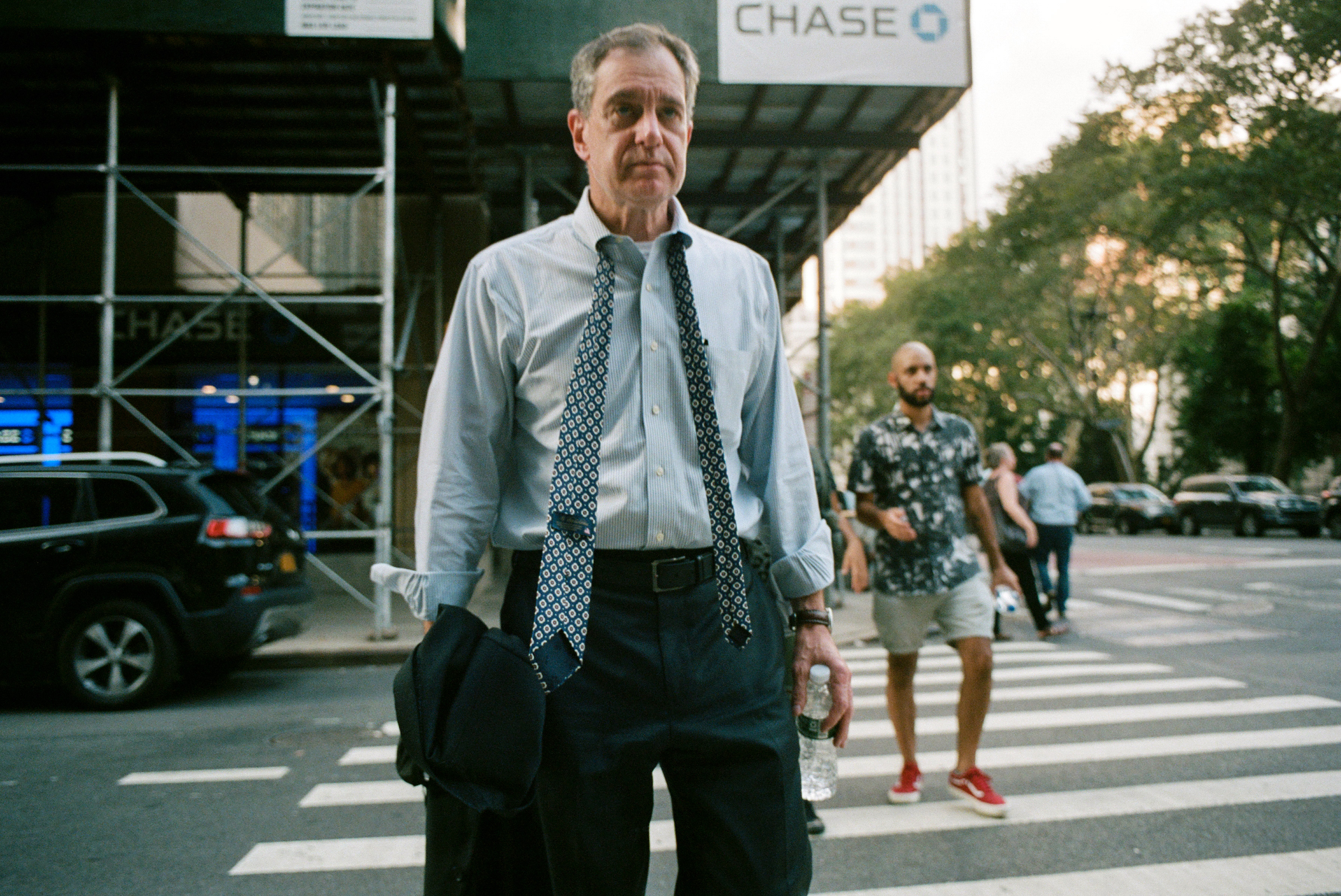 A man with his tie unfurled crosses the street in downtown Manhattan, Aug. 26, 2021.