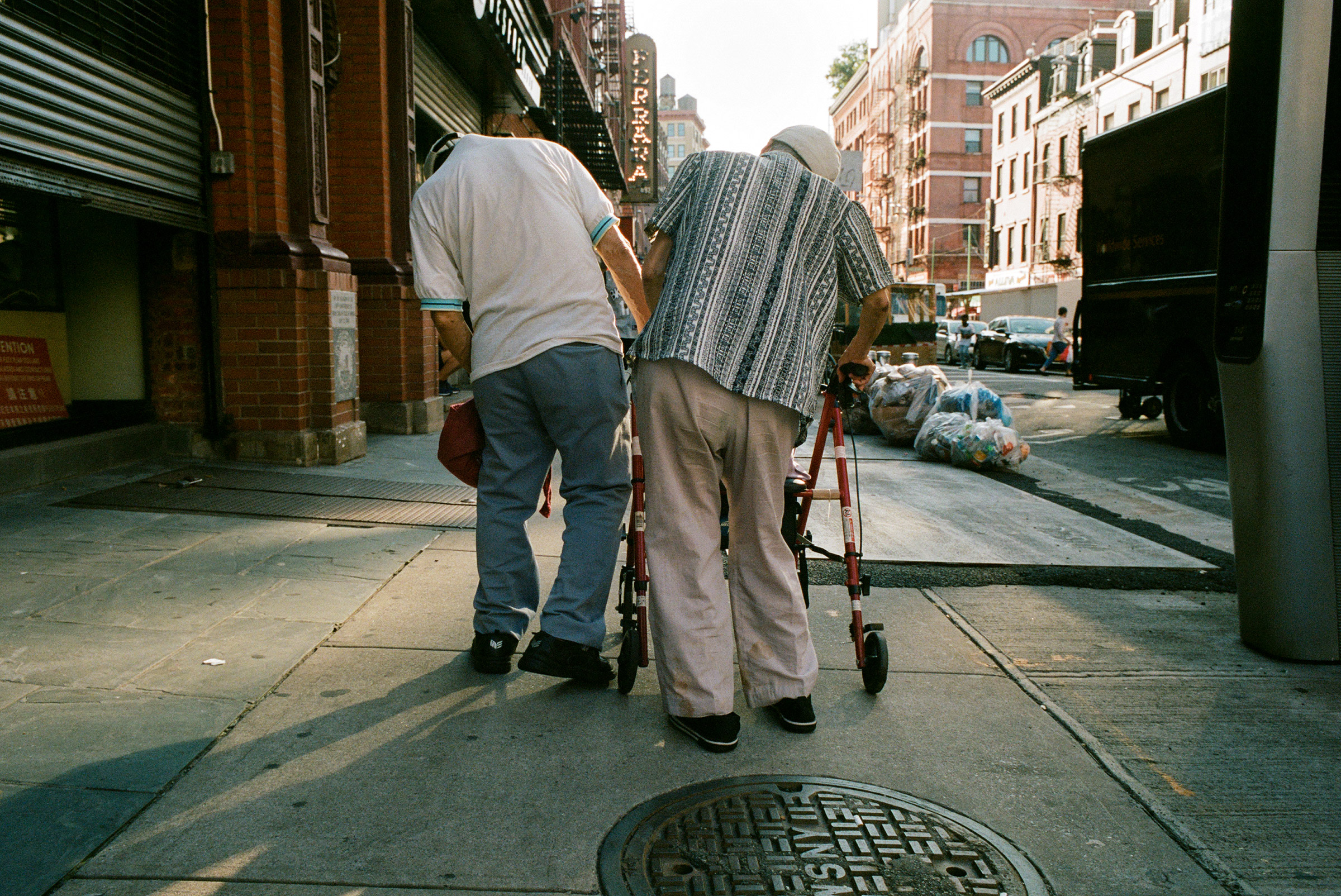 Pedestrians lean on each other in Chinatown, Aug. 27, 2021.