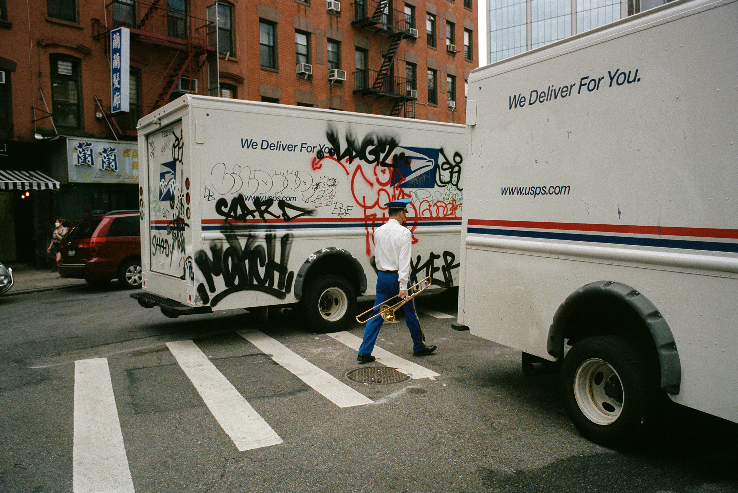 A trombonist from a Chinatown funeral band slips between mail trucks, Sept. 4, 2021.