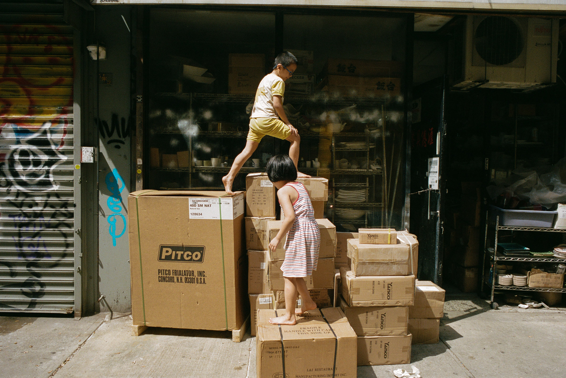 Kids climb on stacks of boxed kitchenware at the corner of Ludlow and Hester Streets, Sept. 1, 2021.