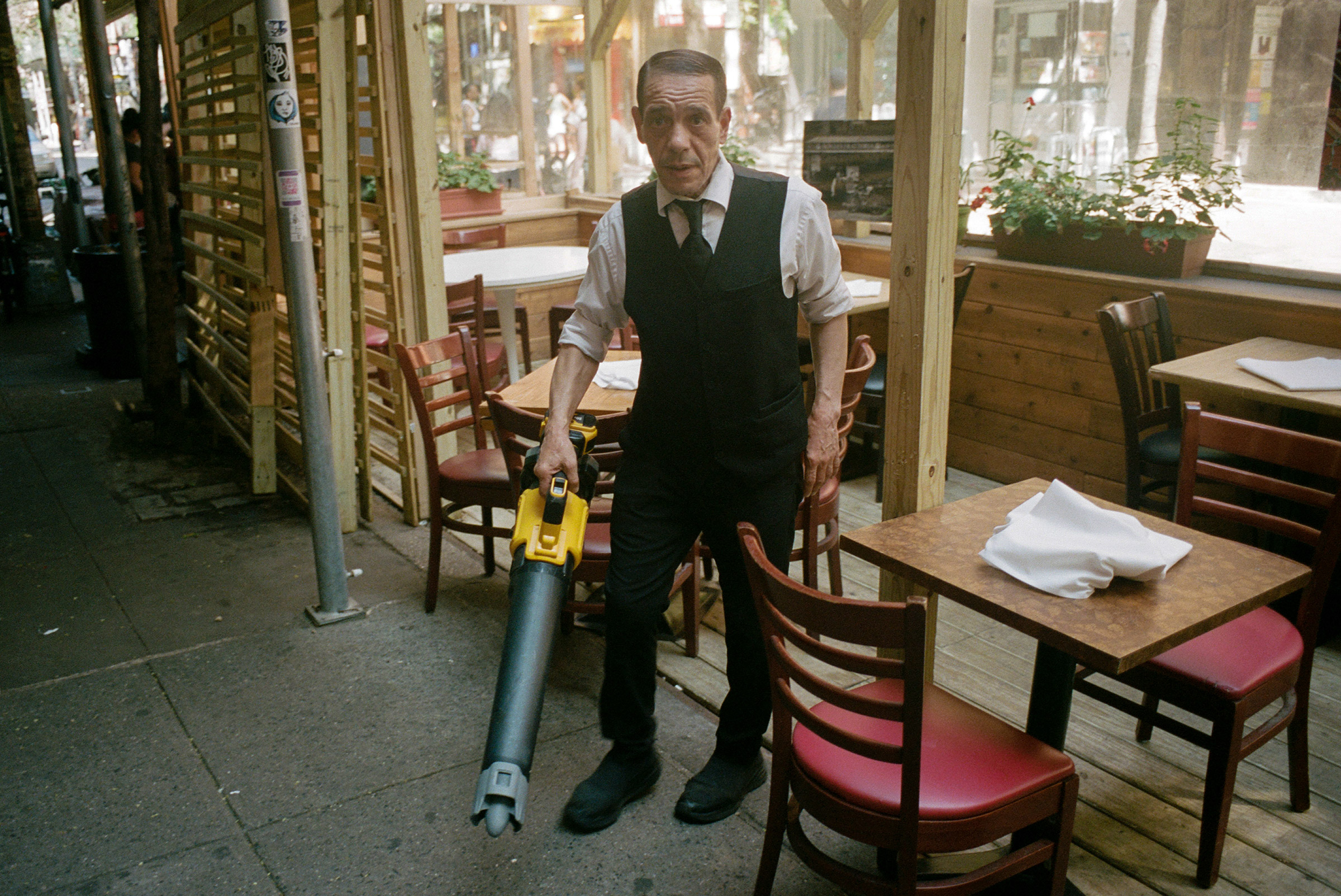 A maître d' cleans an outdoor seating area with a blower before evening service on MacDougal Street, Aug. 12, 2021.