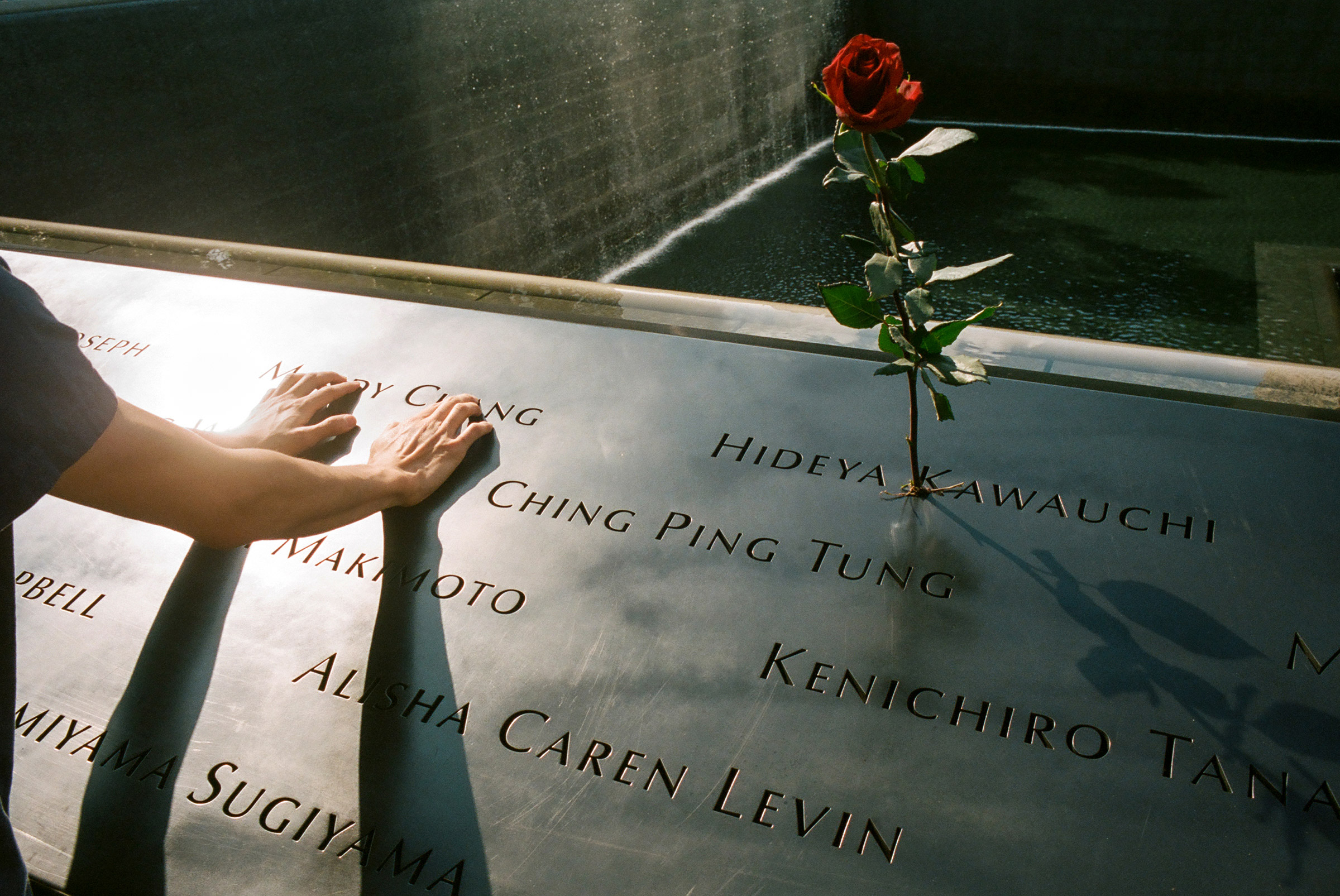 A mourner clings to the name of a lost loved one at the 9/11 memorial, Sept. 11, 2020.