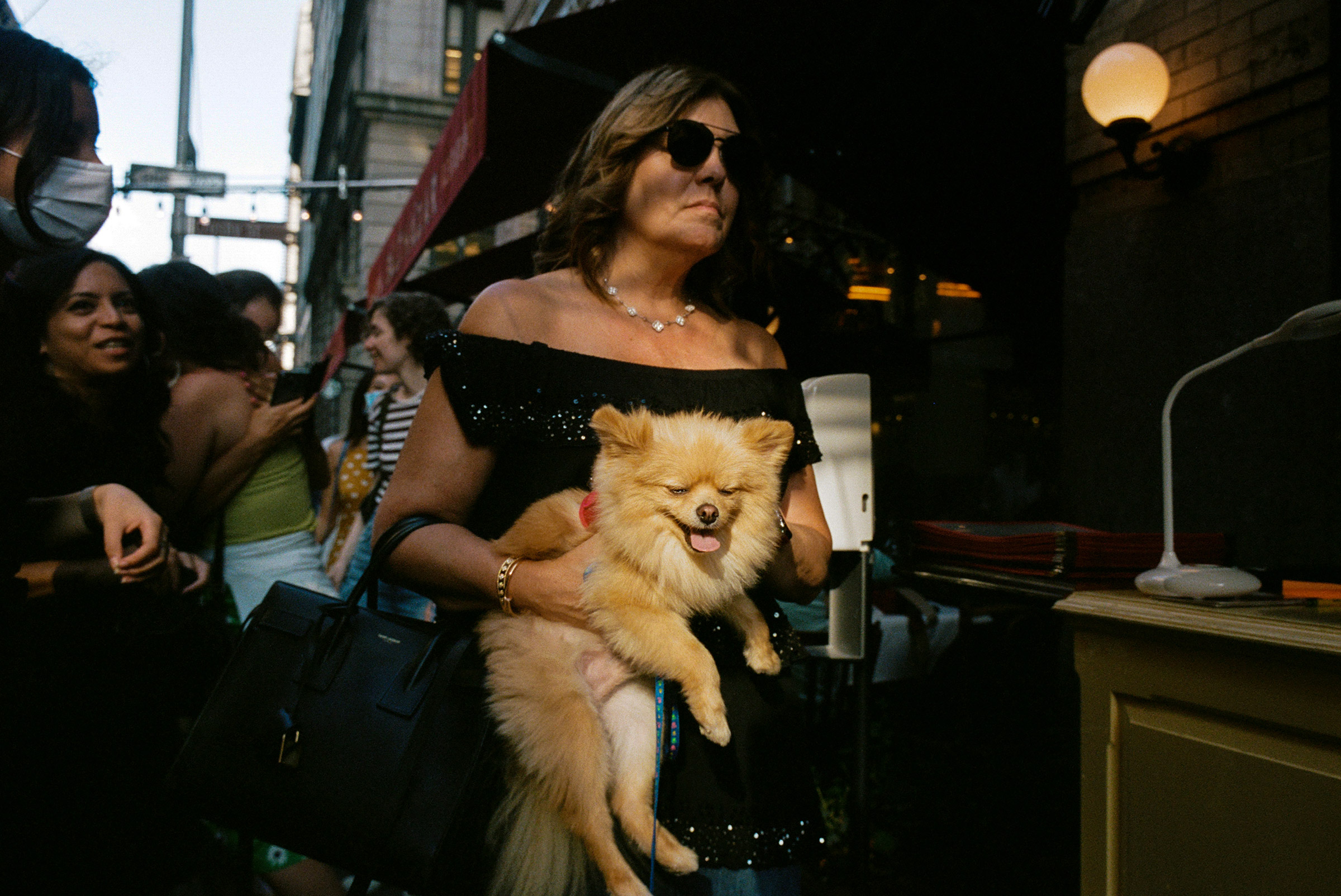A woman carries her Pomeranian past Balthazar at sunset on Spring Street, Aug. 1, 2021.