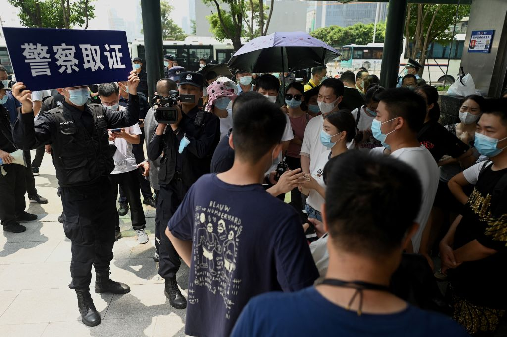Police officers survey people gathering at the Evergrande headquarters in Shenzhen, China on Sept. 16, 2021, as the Chinese property giant said it was facing  unprecedented difficulties  but denied rumors that it was about to go under.