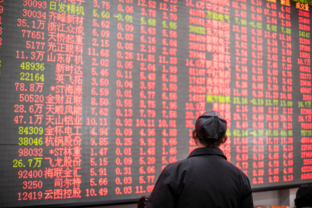 An investor watches an electric screen displaying stock price figures at a stock exchange hall on February 18, 2021 in Shanghai, China.