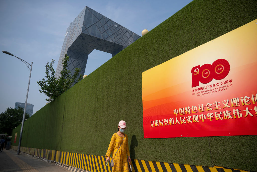 A woman walks past a sign celebrating the centenary of the Communist Party of China, with the CCTV headquarters seen in the background, on June 28, 2021 in the central business district of Beijing.