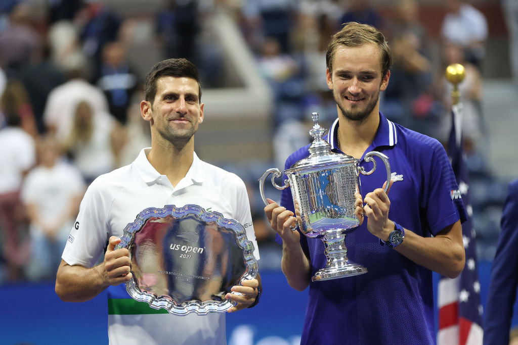 Novak Djokovic of Serbia holds the runner-up trophy alongside Daniil Medvedev of Russia who celebrates with the championship trophy after winning their Men's Singles final match on Day Fourteen of the 2021 US Open at the USTA Billie Jean King National Tennis Center on September 12, 2021 in New York City.  (Photo by Matthew Stockman/Getty Images)
