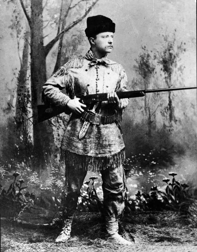 A full-length studio portrait of Theodore Roosevelt (1858 - 1919), president of the United States from 1901 to 1909, wearing hunting gear and holding a Winchester gun in an artificial forest setting, circa 1900.