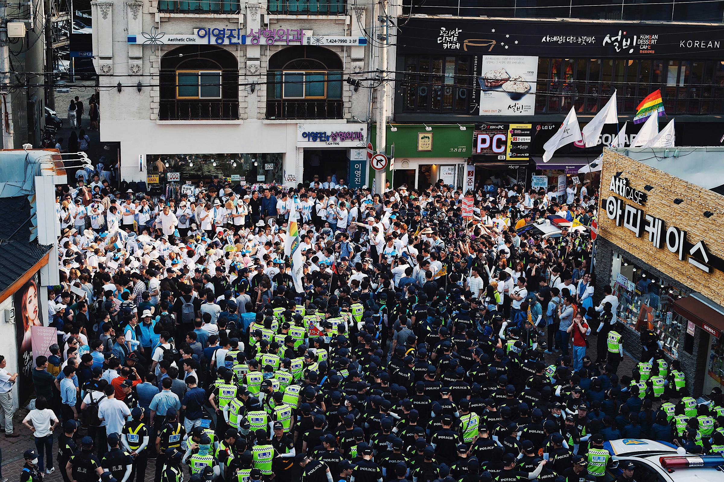 2018년 6월, 대구퀴어문화축제 반대시위 참가자들이 하얀색 옷을 입고 퍼레이드행렬을 막고 있는 모습이다. 500명이 넘는 기독교 신자들이 동성로 광장 도로에서 애국가를 부르며 퍼레이드를 취소시키기 위해 좌식농성을 하고있다.