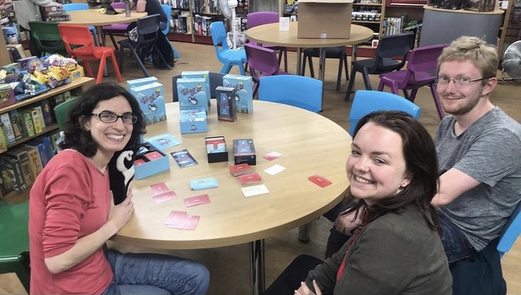 Molly Zeff playing Wing It with two customers at the Fan Boy Three game store in Manchester, England, in 2019.