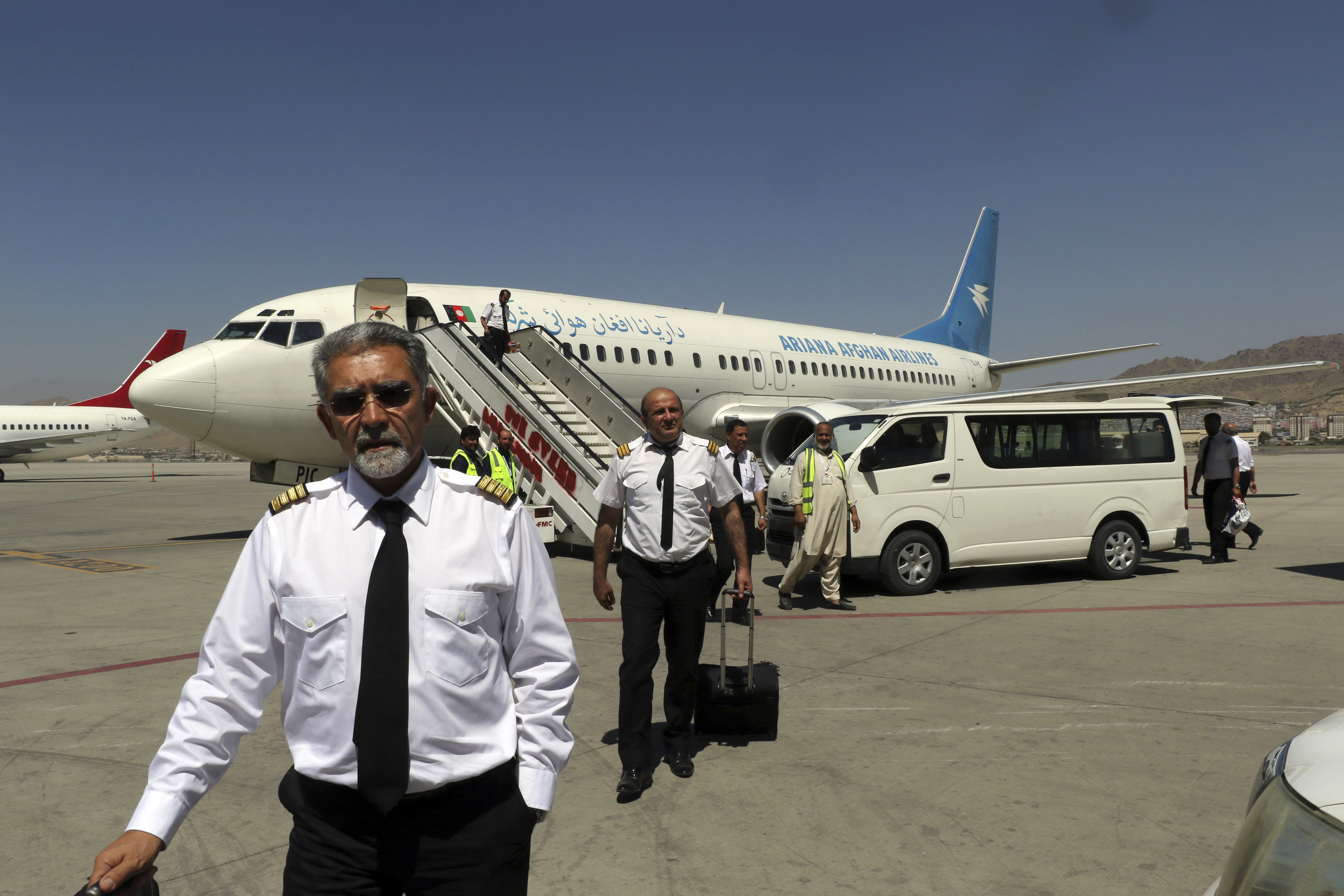 Pilots of Ariana Afghan Airlines walk on the tarmac after landing at Hamid Karzai International Airport in Kabul, Afghanistan, on Sept. 5, 2021.