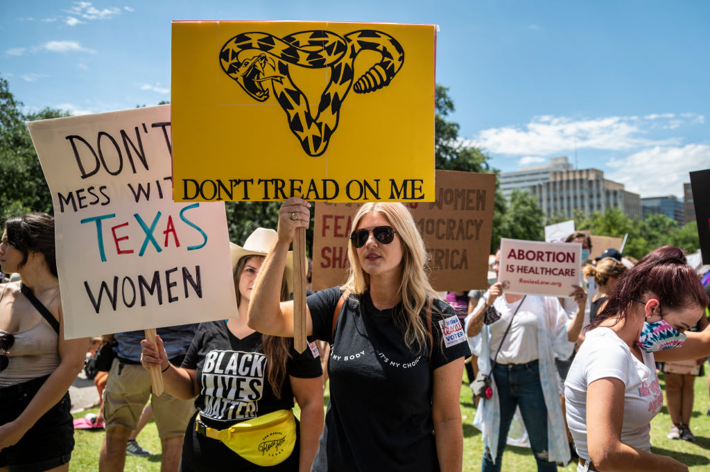 Protesters hold up signs at a protest outside the Texas state capitol on May 29 in Austin.