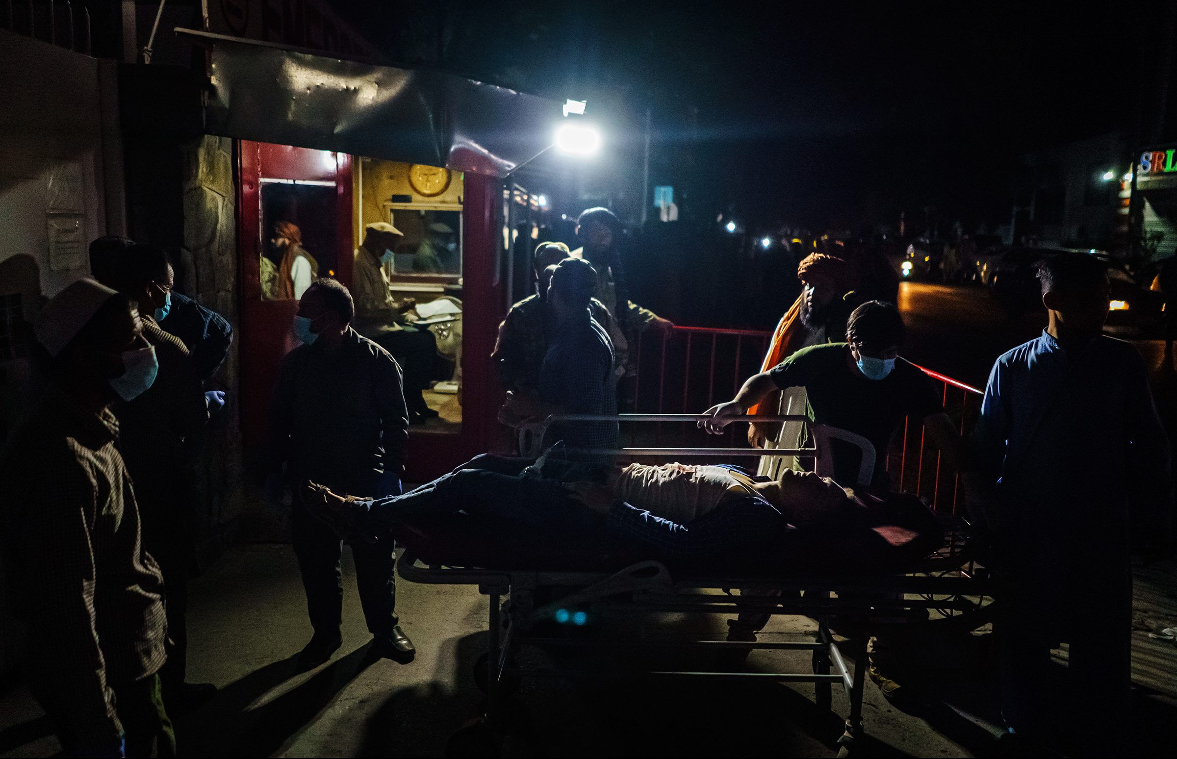 Hospital staff help bring in a wounded patient brought by an ambulance at an emergency hospital in Kabul, Aug. 26. Twin bombings struck near the entrance to Kabul's airport on Thursday.