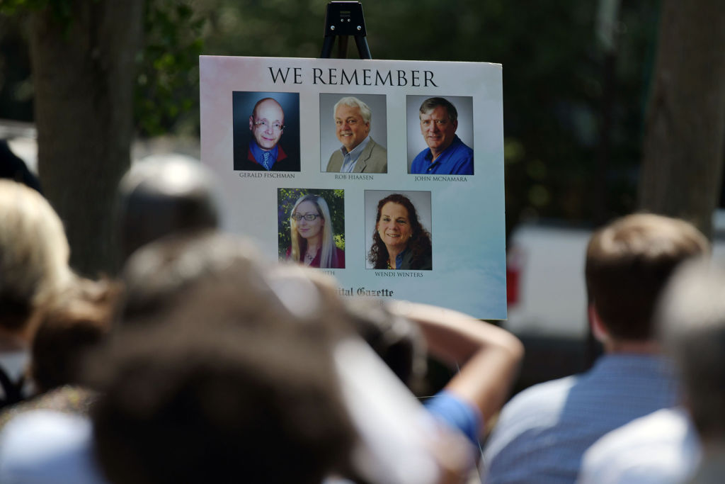 Photos of Gerald Fischman, Rob Hiaasen, John McNamara, Rebecca Smith and Wendi Winters, five people who were killed at the Capital Gazette one year ago, are displayed at the dedication of a Memorial Garden at the Actons Cove Waterfront Park.
