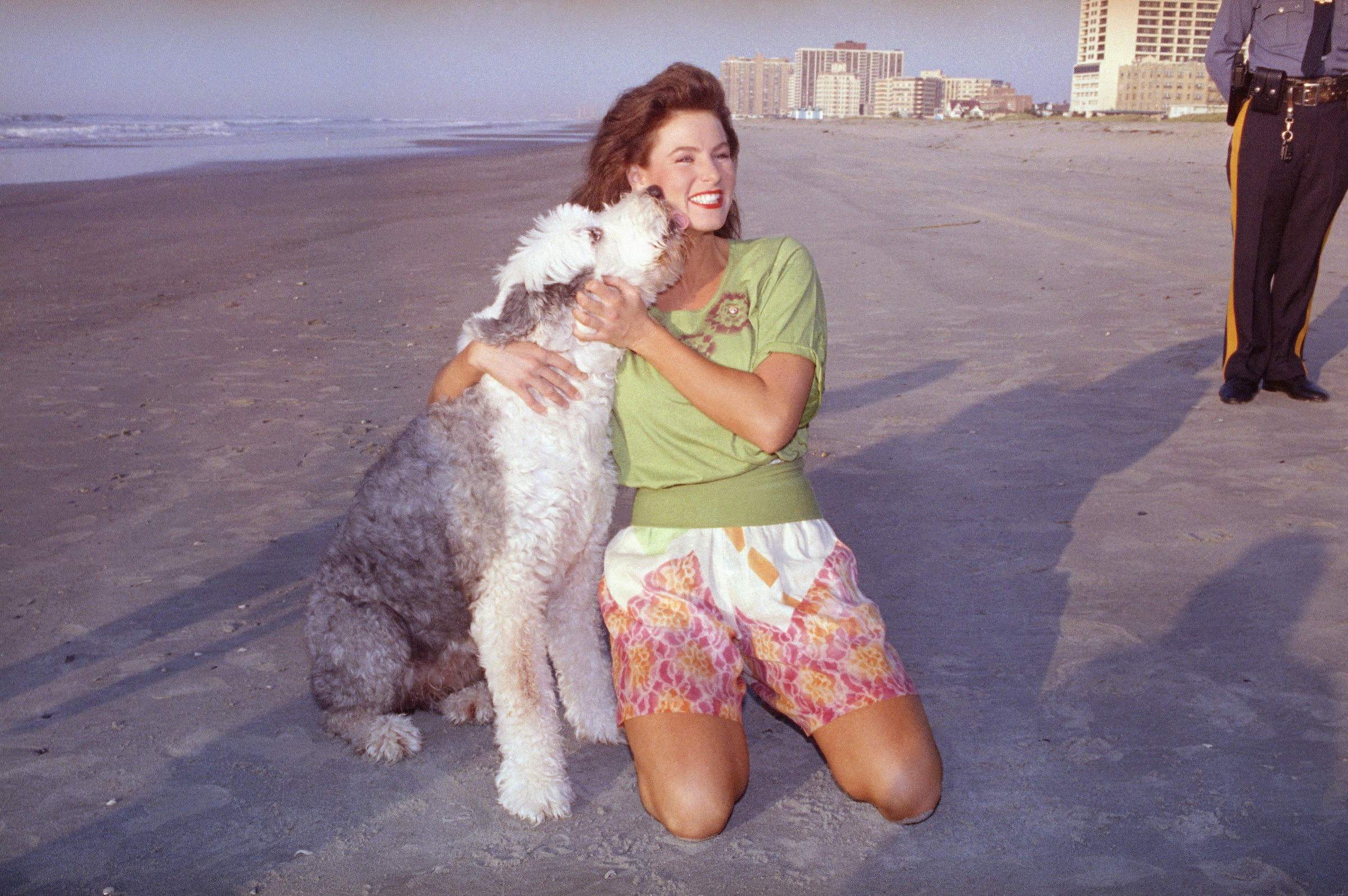 Jade, an Old English sheepdog, licks the face of the newly-crowned Miss America, Carolyn Sapp, during the traditional walk on the beach in Atlantic City, N.J. on Sept, 15, 1991.