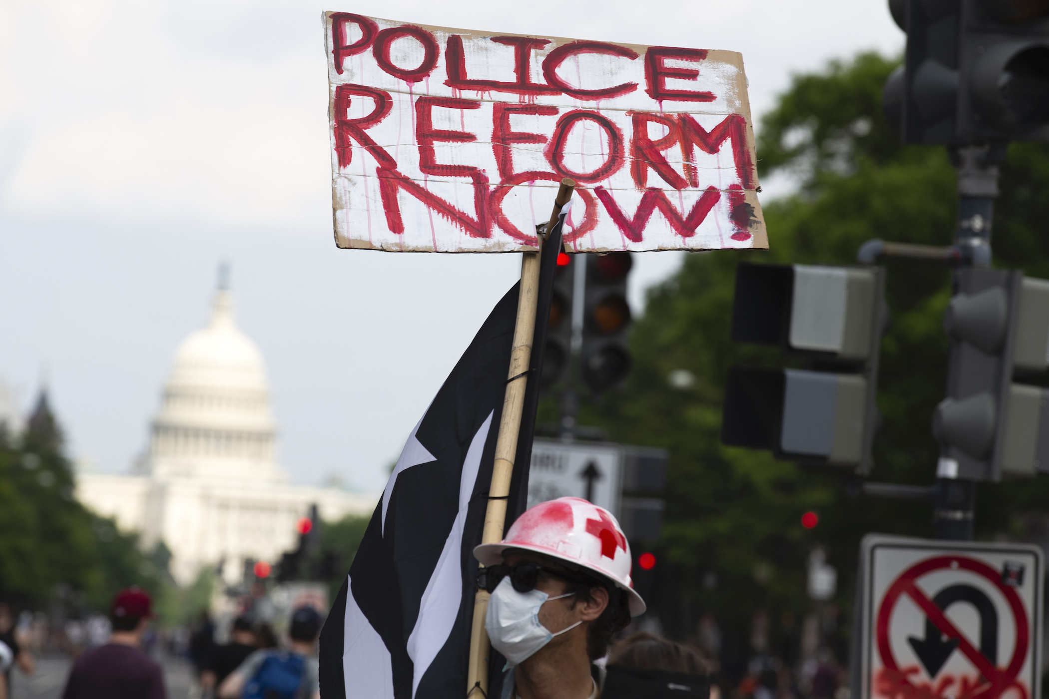 A demonstrator holds a placard during a march against racism and police brutality, in Washington, D.C. on June 6, 2020.