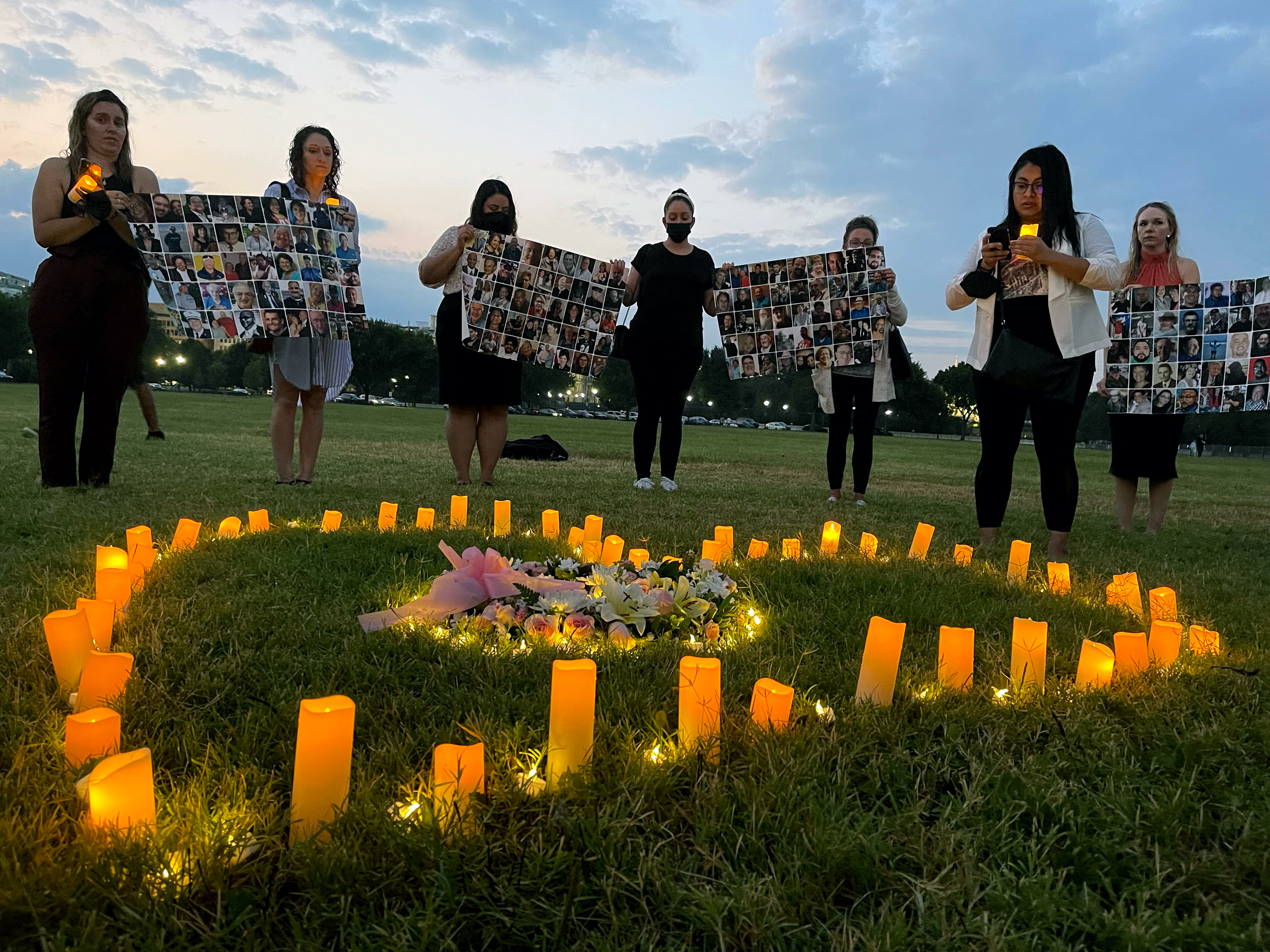 Activists lobbying in Washington D.C. hold up images of lost loved ones at a lighting ceremony on July 26, 2021.