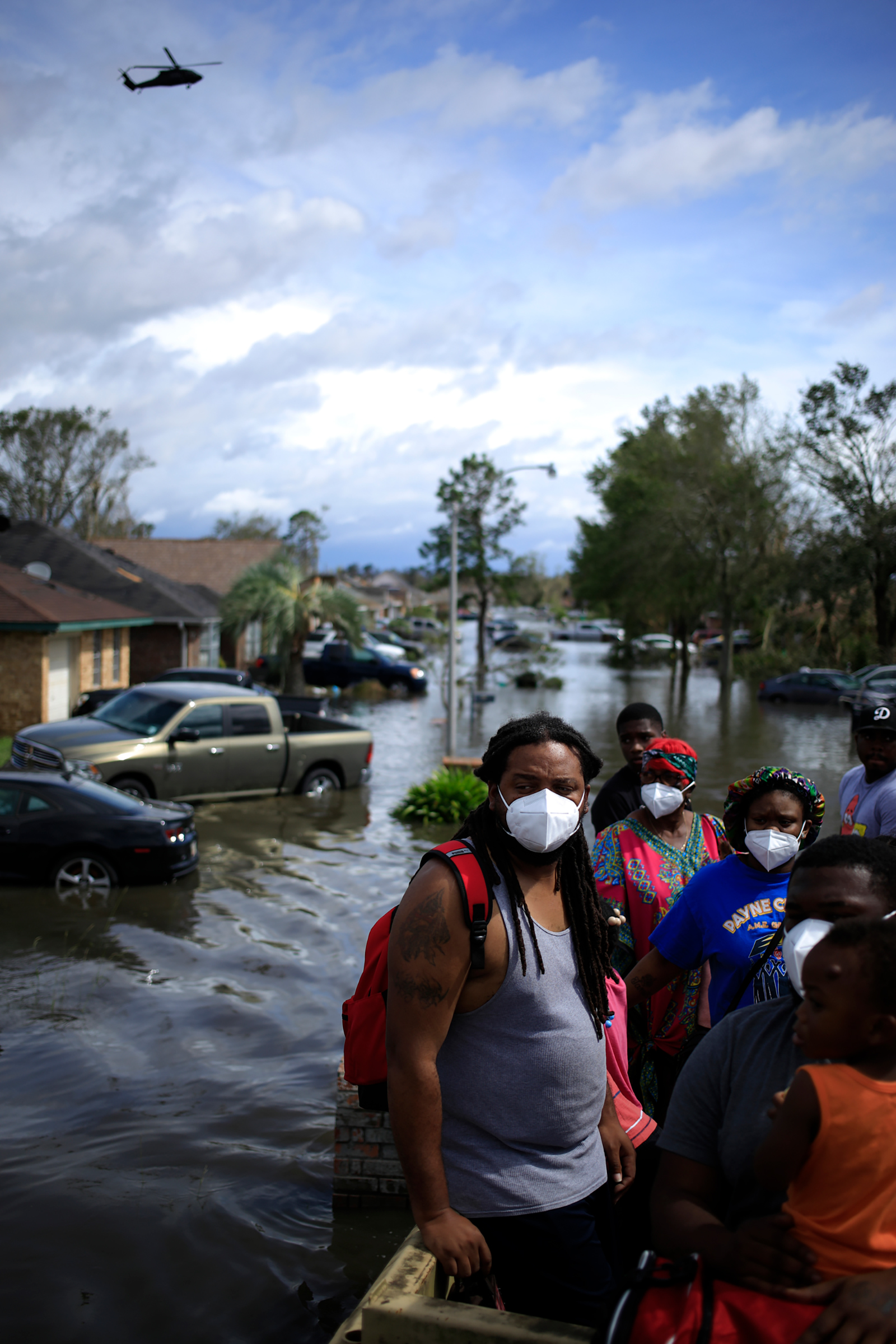Residents ride in a high water vehicle after being rescued from floodwater left behind by Hurricane Ida in LaPlace, La. on Aug. 30.