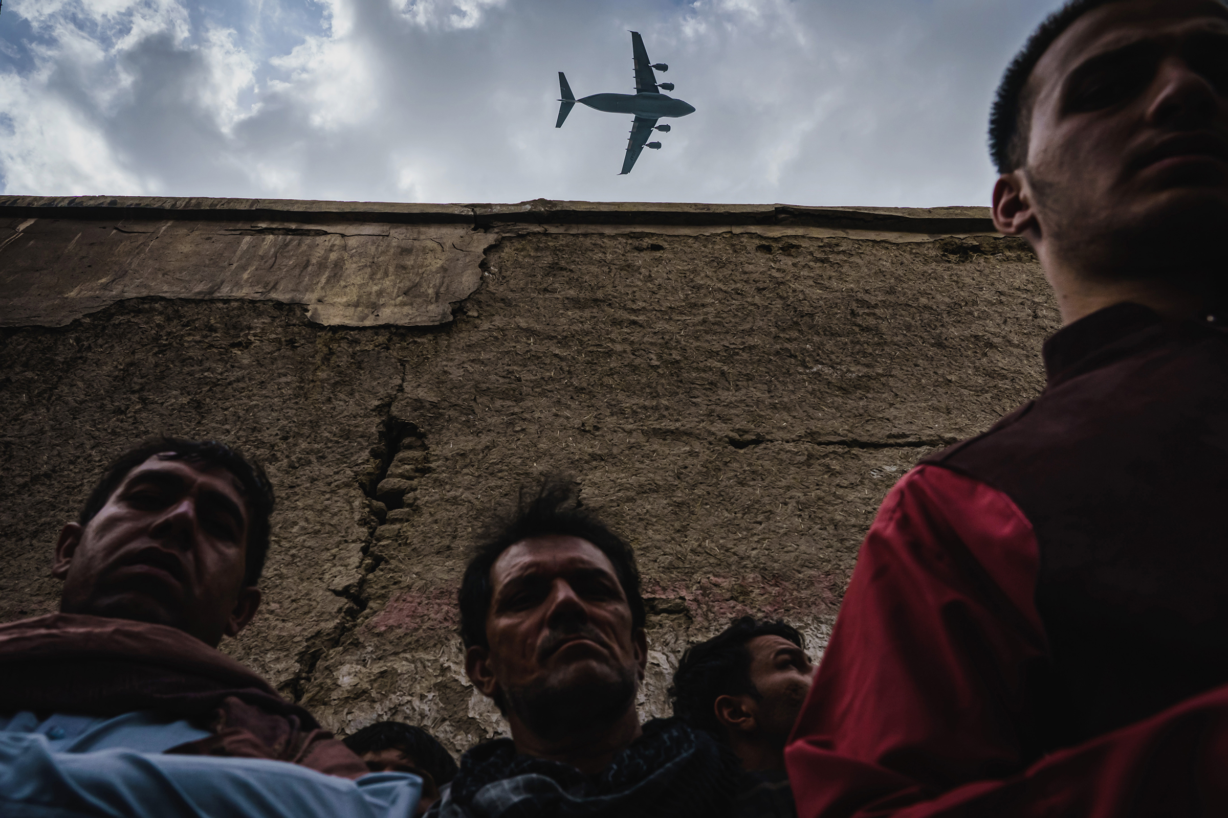 A military transport plane flies over relatives and neighbors of the Ahmadi family, who had gathered around the vehicle that was destroyed, on Aug. 30.