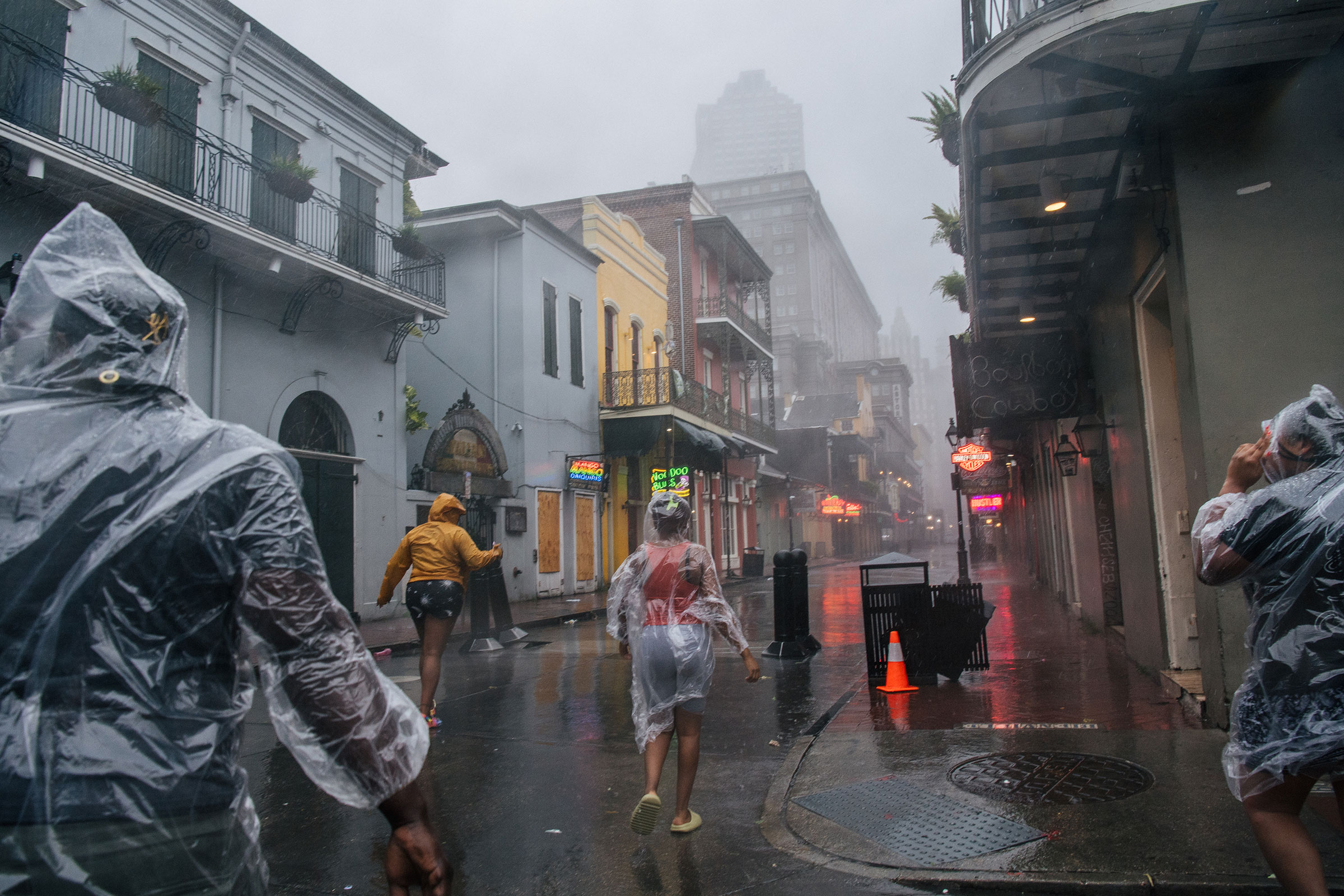 A group of people walk through the French District during Hurricane Ida in New Orleans on Aug. 29, 2021.