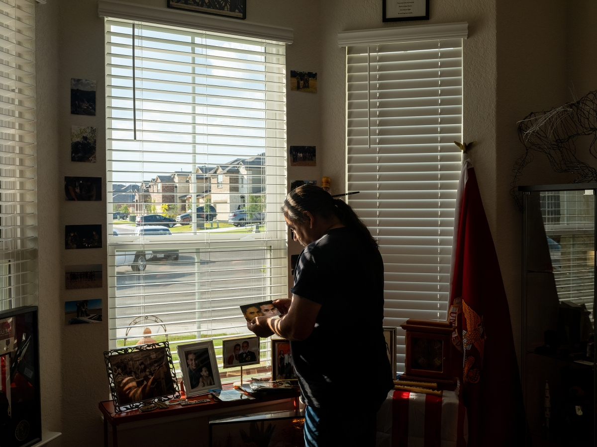 On one of the final days of the U.S. evacuation from Afghanistan, Javier Gutierrez studies a photo of his son.
