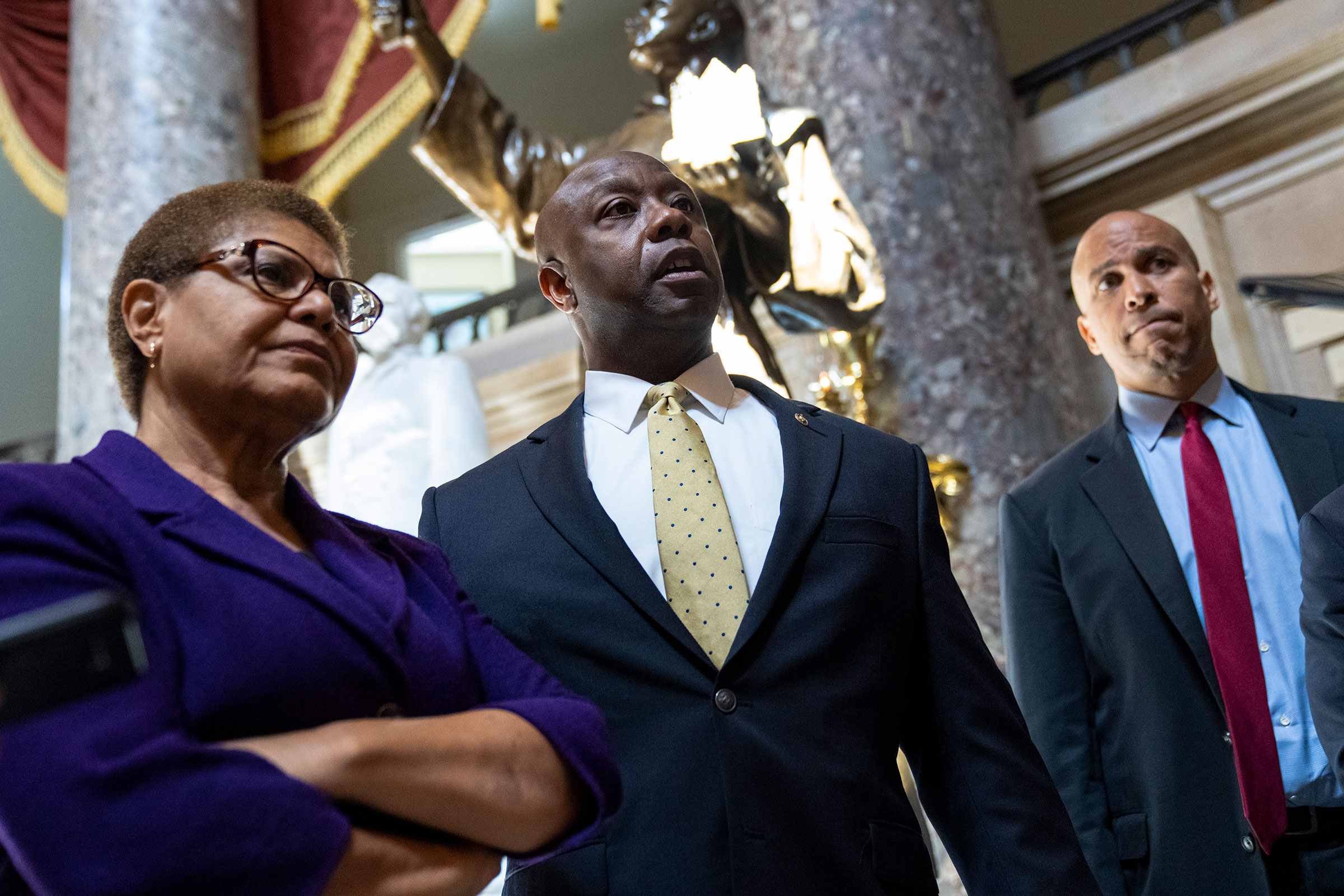 Rep. Karen Bass, Sen. Tim Scott, and Sen. Cory Booker speak briefly to reporters as they exit the office of Rep. James Clyburn following a meeting about police reform legislation on Capitol Hill on May 18, 2021.