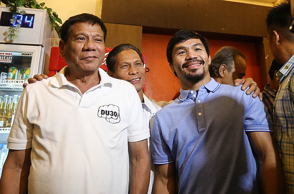 Philippines' President Rodrigo Duterte (L) stands beside boxing icon and Senator Manny Pacquiao (R) at a meeting in Davao in southern island of Mindanao on May 28, 2017.