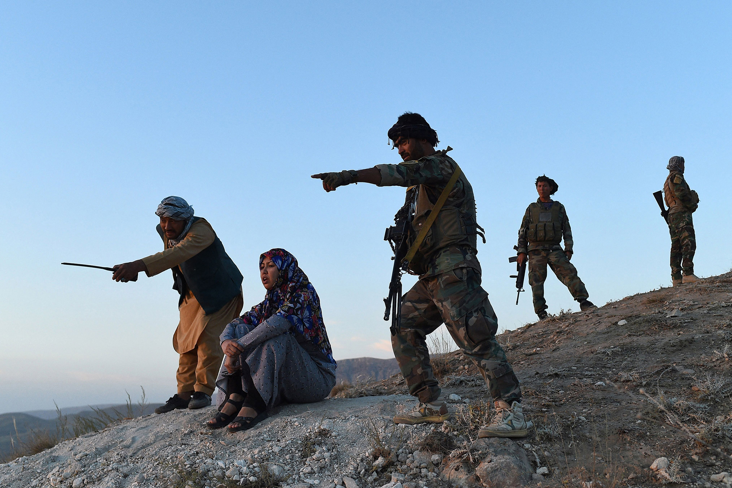 District governor Salima Mazari (second from left) looks on from a hill while accompanied by security personnel near the frontlines against the Taliban, at Charkint district in Balkh province, Afghanistan, on July 14.